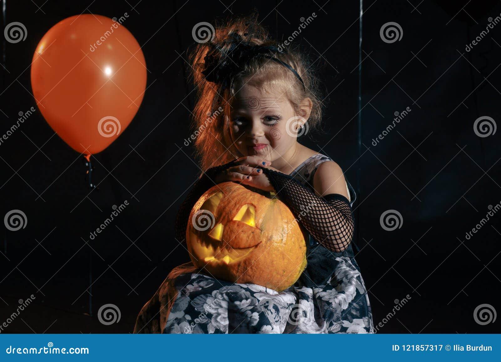 愉快的万圣夜逗人喜爱的矮小的巫婆用南瓜