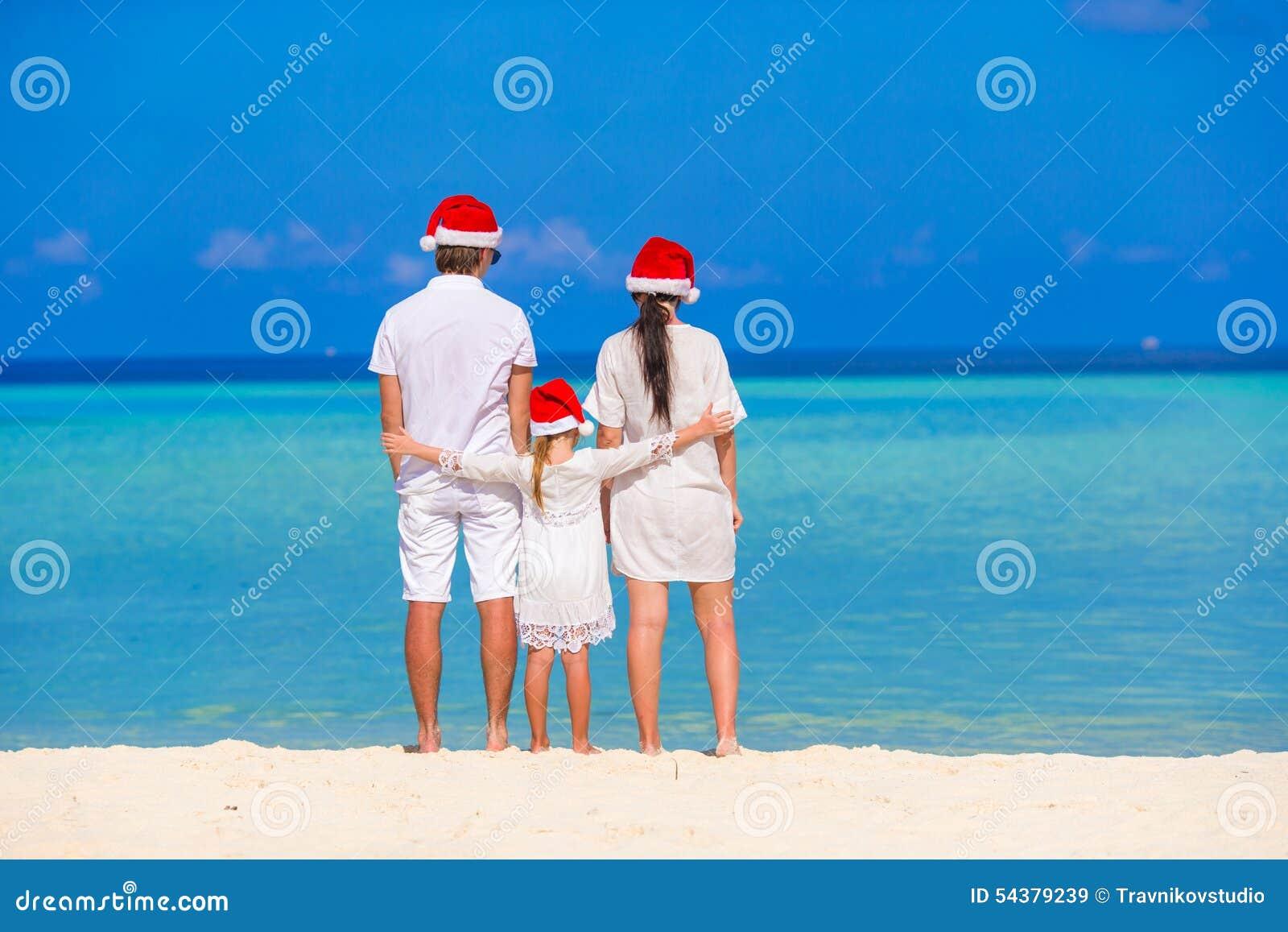 愉快的三口之家在圣诞老人帽子在期间
