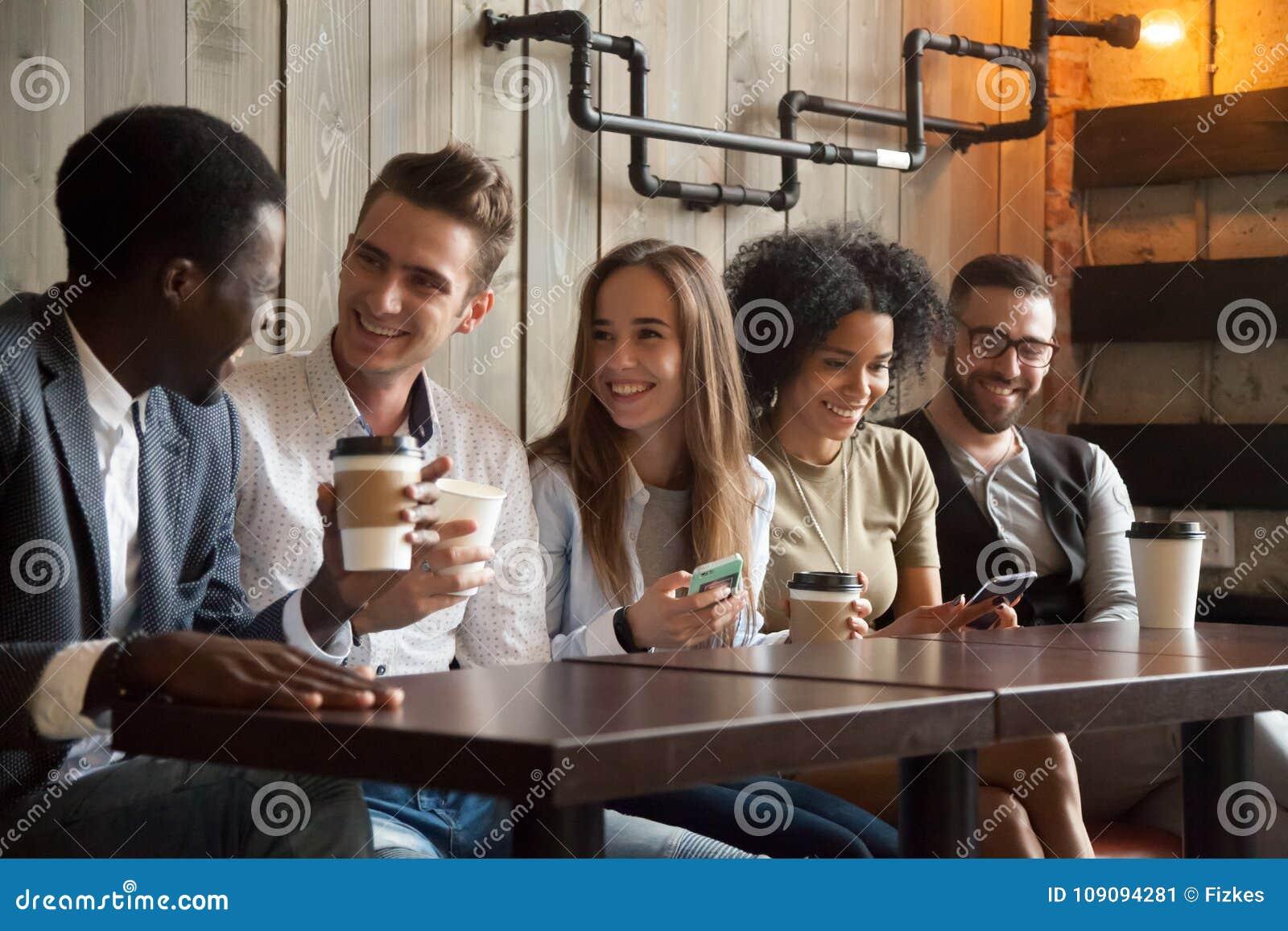 愉快的不同种族的小组朋友谈话使用智能手机在