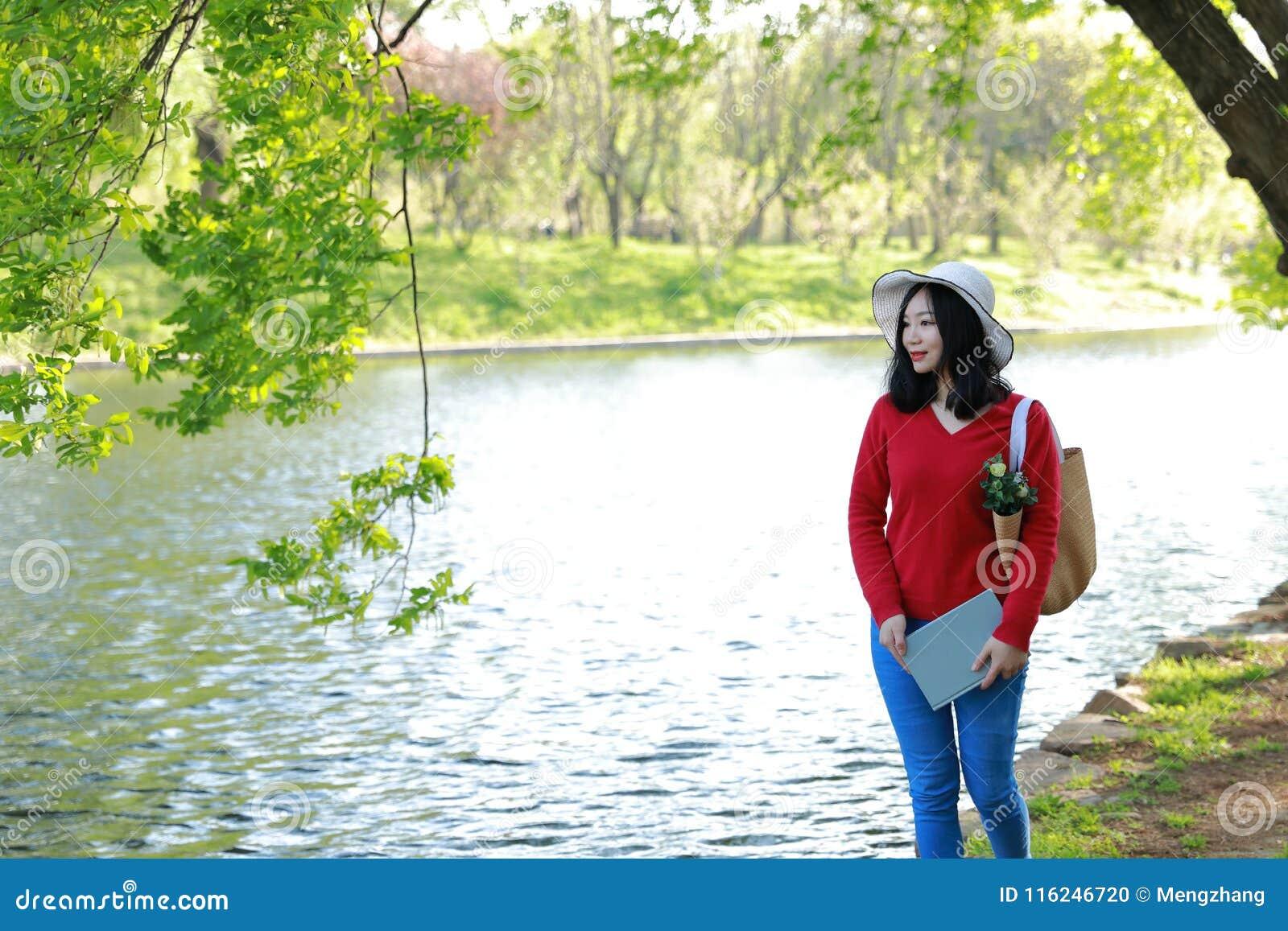 愉快的亚洲中国妇女秀丽女孩微笑由湖读了书步行在森林春天公园坐长凳享有舒适生活