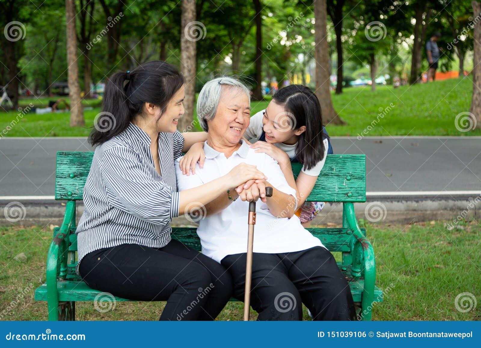 愉快的亚洲家庭在室外公园,微笑的资深妇女坐长凳,当她的女儿和孙女拥抱她时,