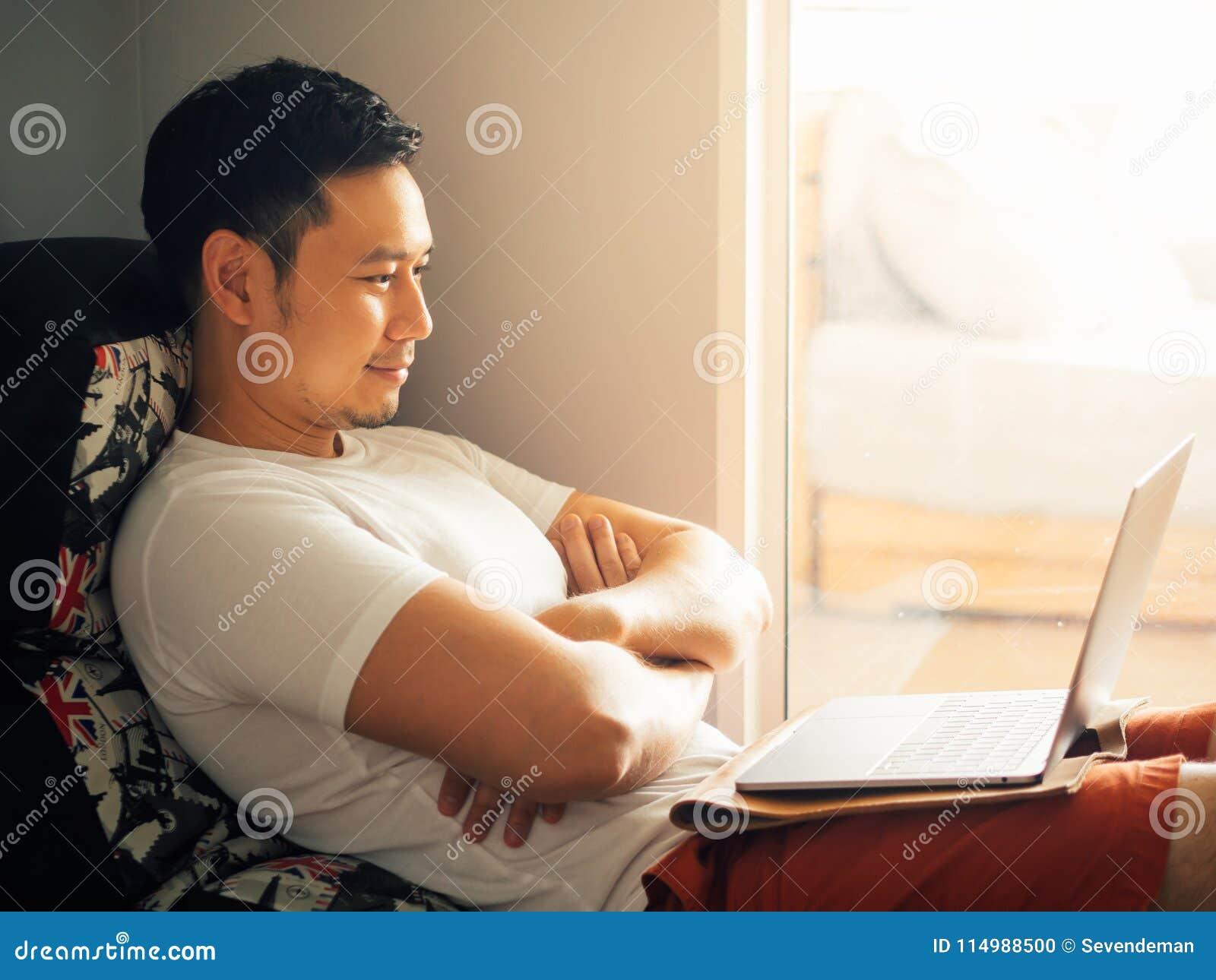 愉快的人早晨使用膝上型计算机并且放松在沙发