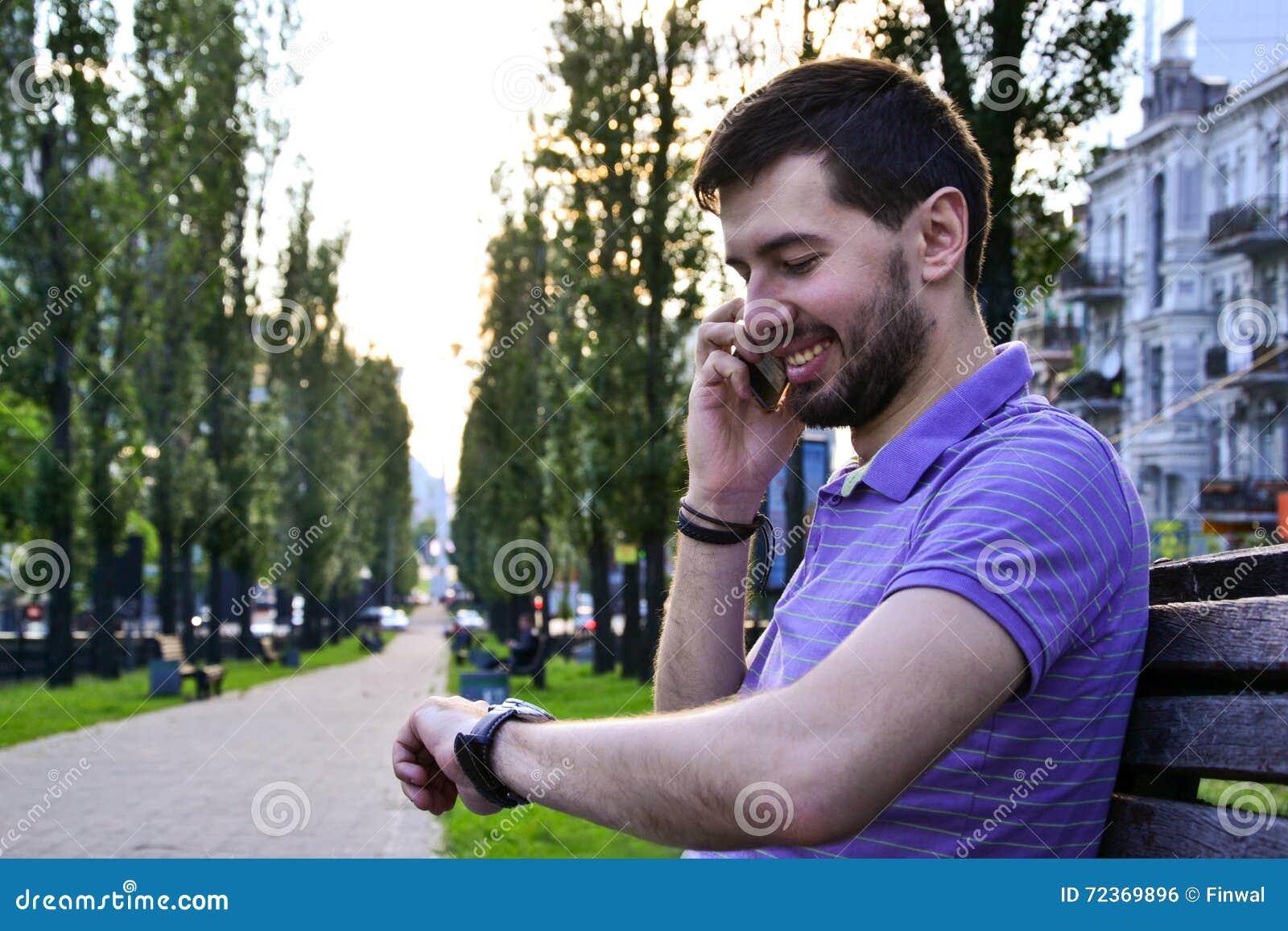 愉快的人谈话在看手表的电话户外