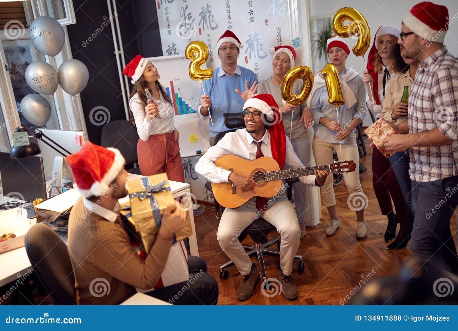 愉快的企业工作者有乐趣和跳舞在圣诞老人帽子在圣诞派对