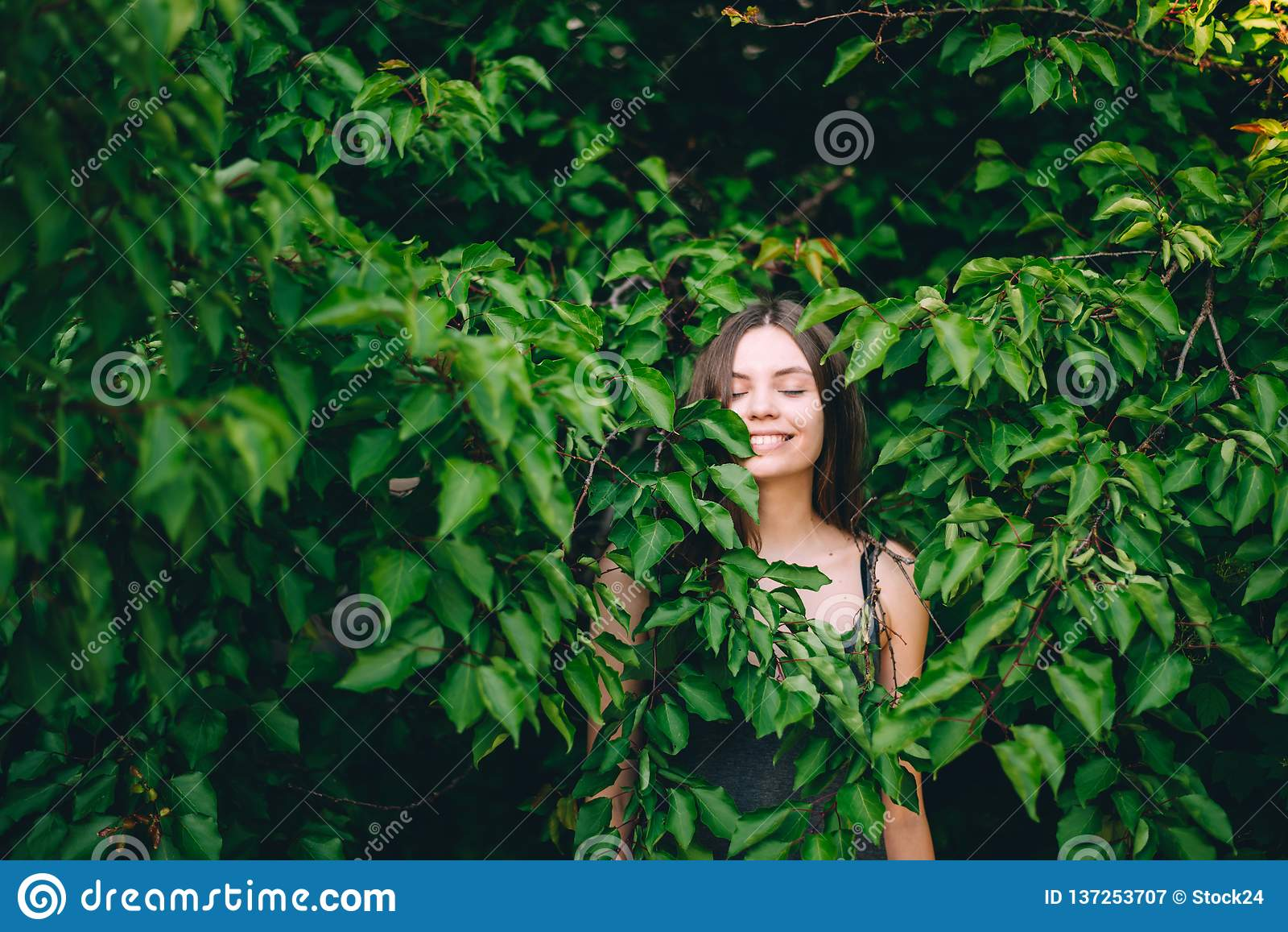 愉快的俏丽的青少年女孩画象绿色叶子微笑的健康自然的