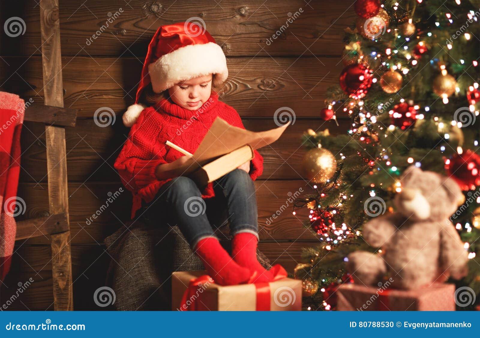 愉快的儿童女孩给圣诞老人写信在圣诞节t