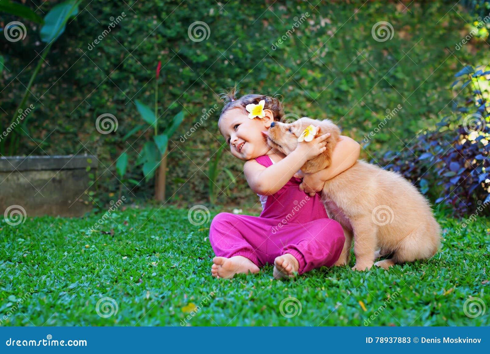 愉快的儿童游戏和拥抱家庭宠物-拉布拉多小狗