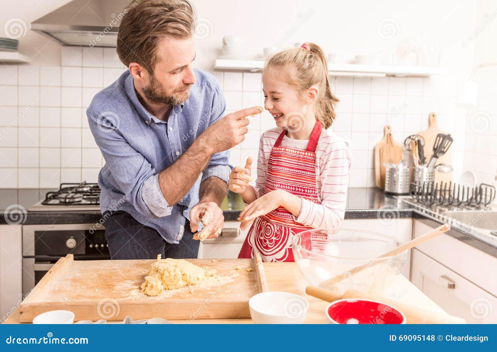 愉快的准备曲奇饼面团的父亲和女儿在厨房里