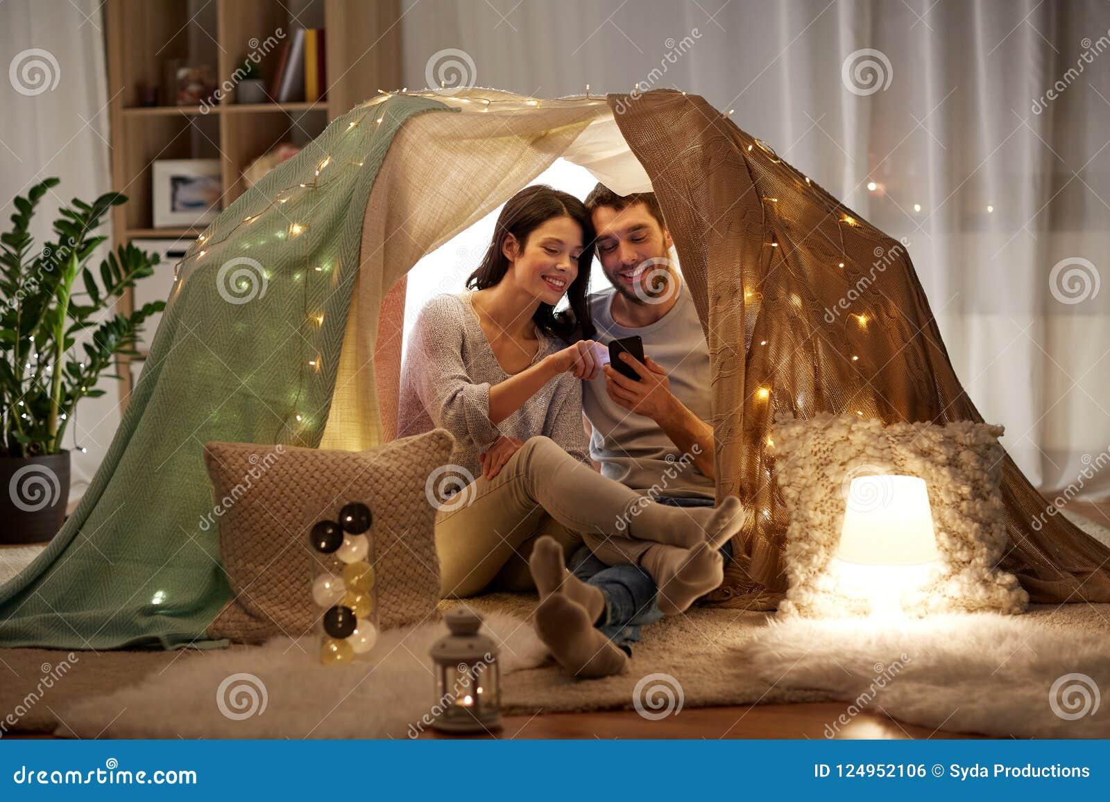 愉快的加上在孩子帐篷的智能手机在家