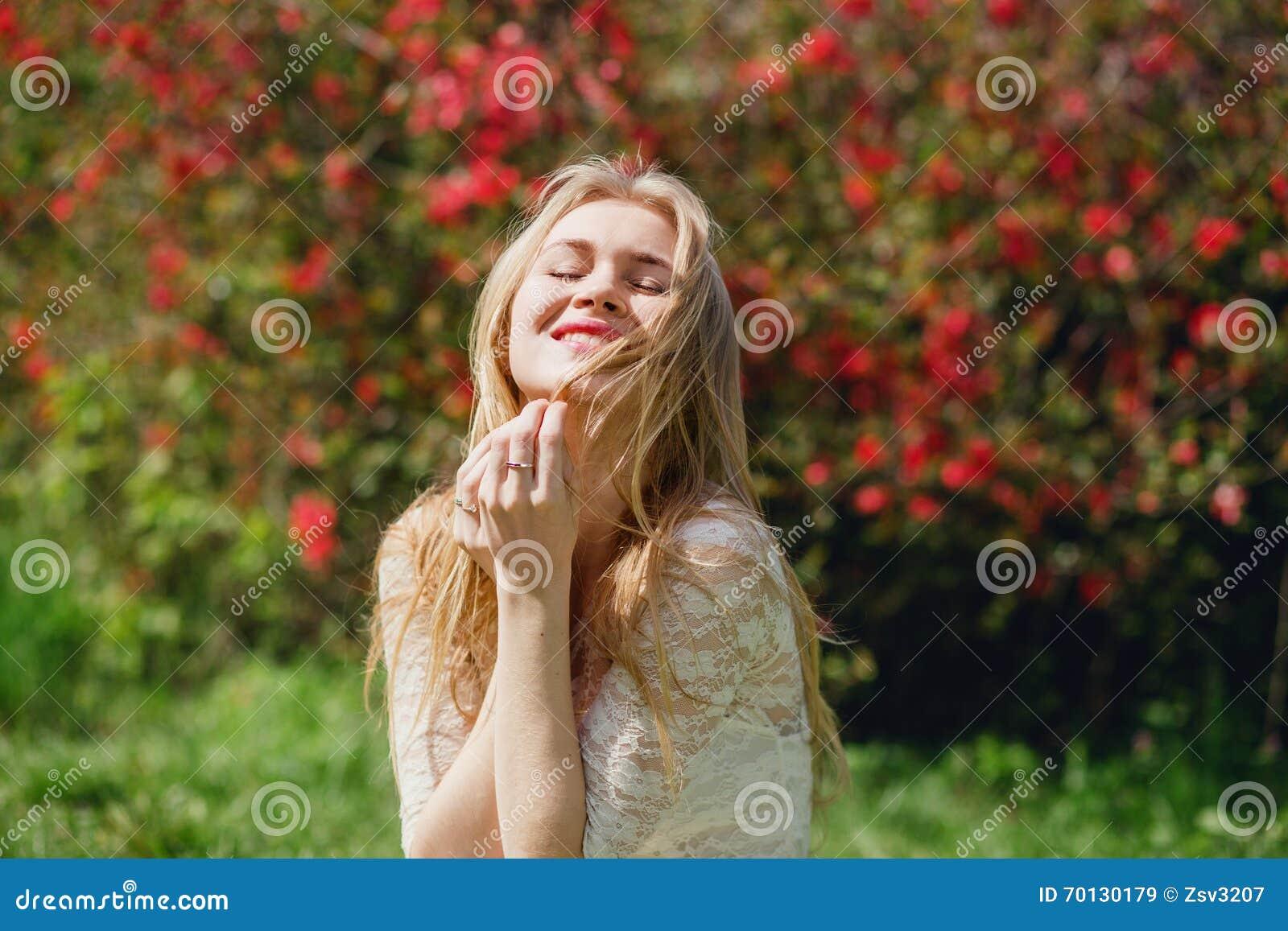 愉快的可爱的白肤金发的女性开会在开花的庭院,有闭合的眼睛的妇女里享受自然,放松的秀丽在