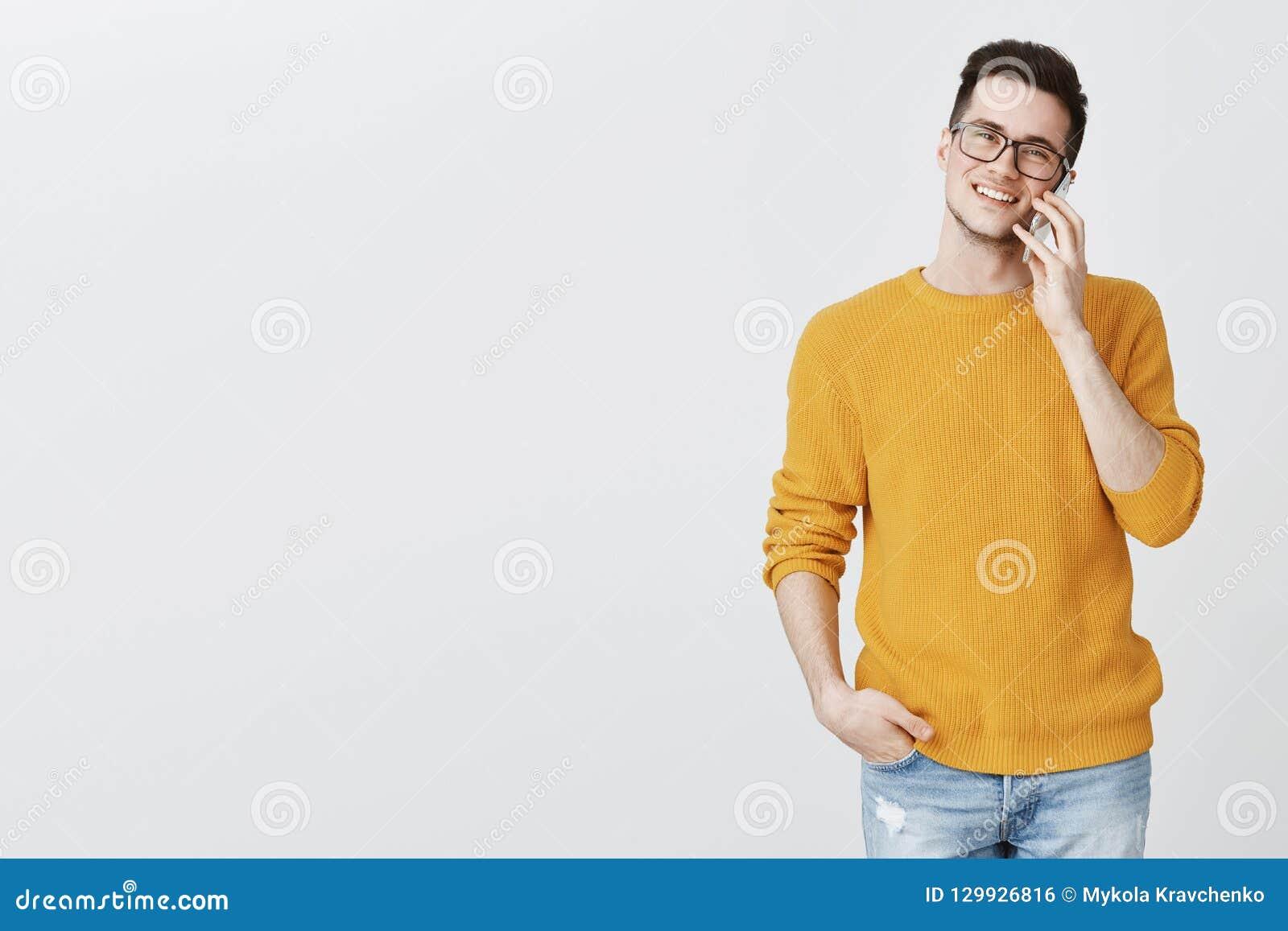愉快的吸引人年轻帅哥画象玻璃和黄色时髦毛线衣藏品手的在轻松的口袋和