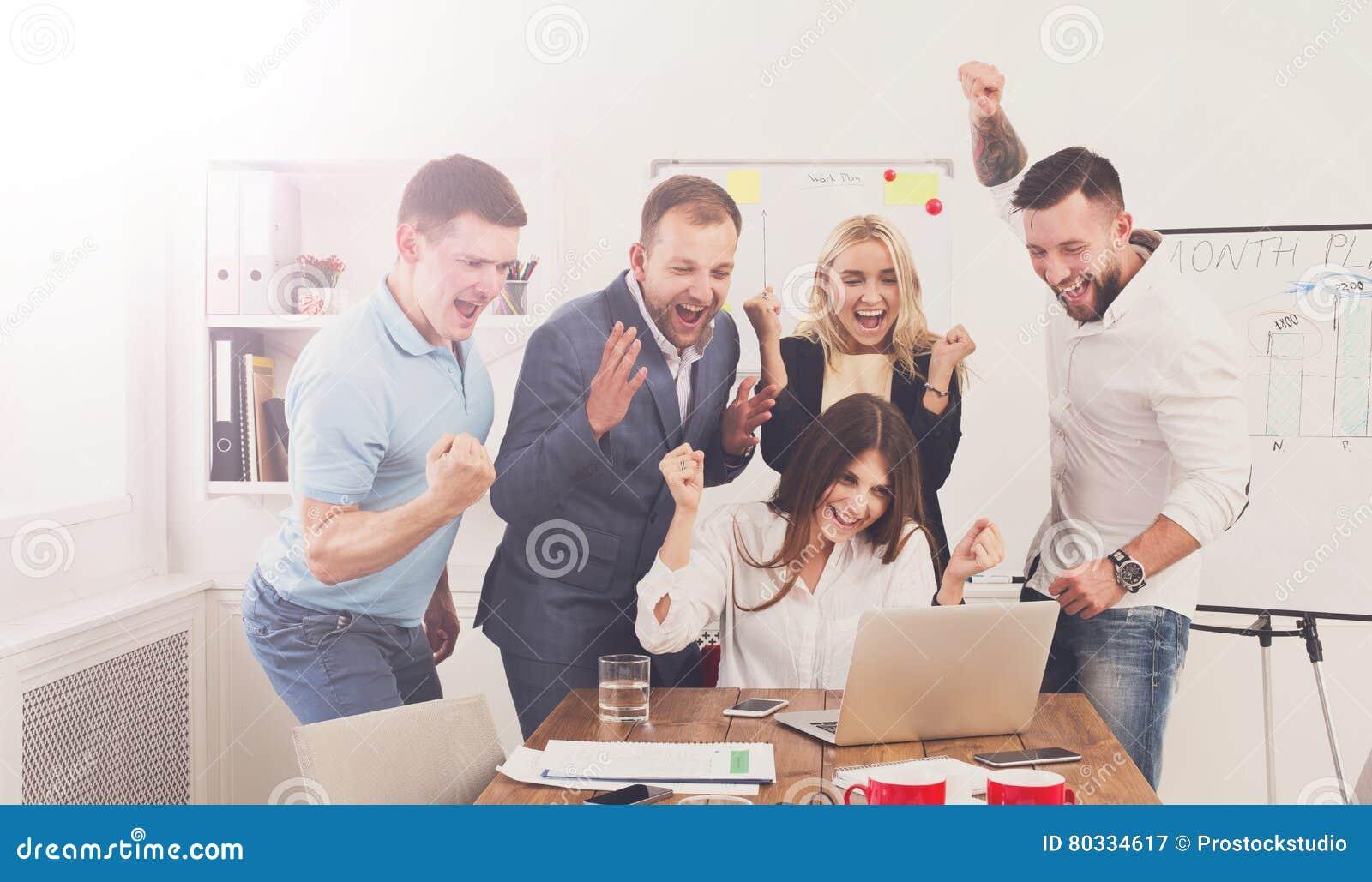 愉快的商人队在办公室庆祝成功