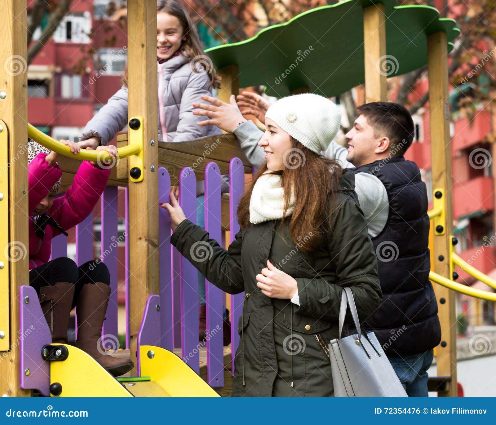 愉快的四口之家在儿童的游乐场
