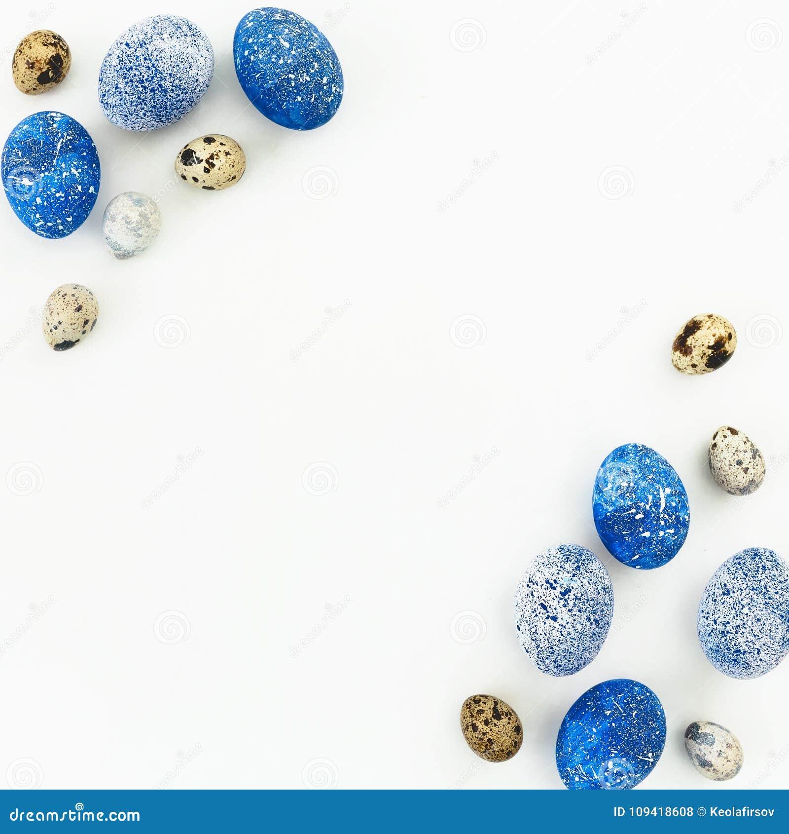 愉快的复活节 框架用蓝色有斑点的复活节彩蛋和鹌鹑蛋与拷贝空间在白色背景 平的位置,顶视图