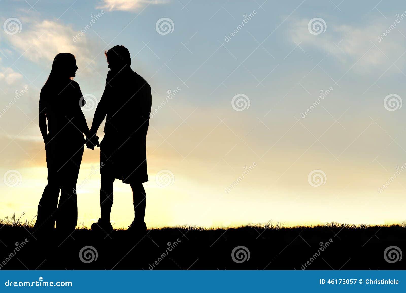 愉快的夫妇剪影握手和谈话在日落