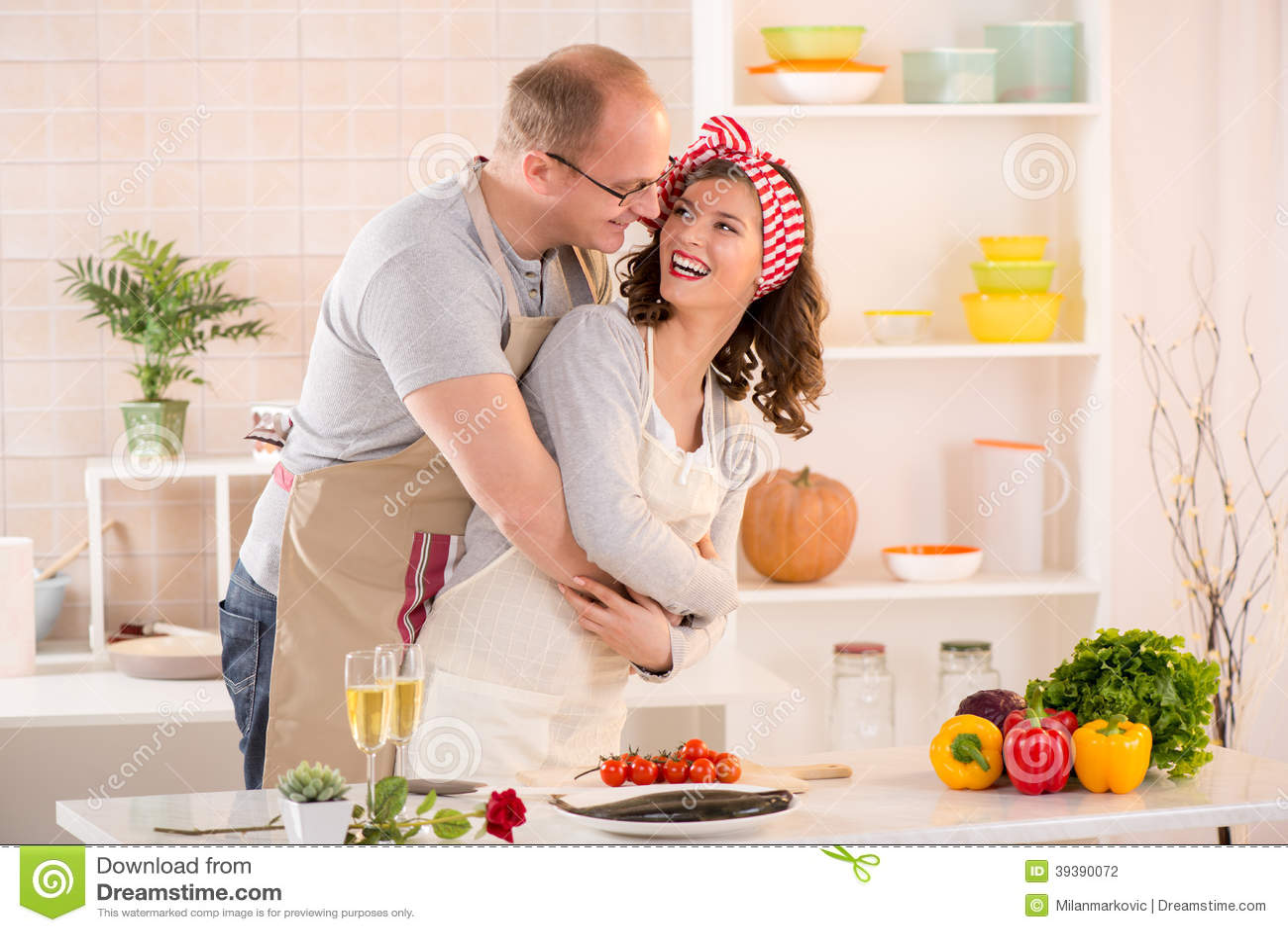 拥抱她的女朋友的愉快的男朋友在厨房里.图片