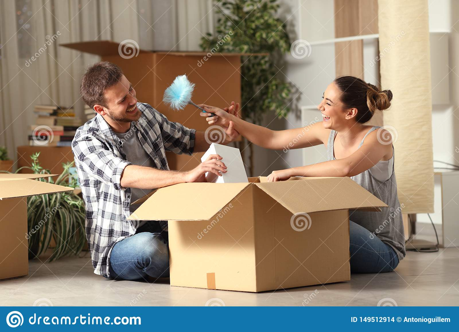 愉快的夫妇耍笑的箱中取出的财产移动的家