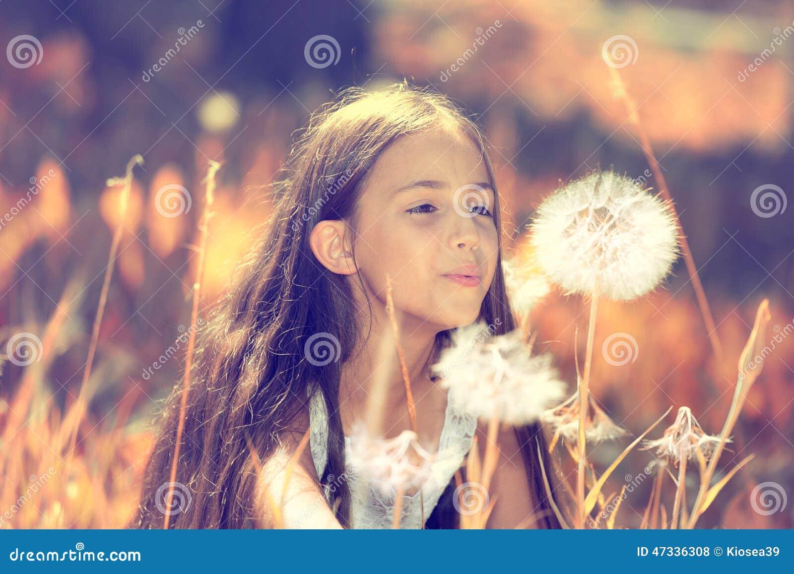 愉快的女孩吹的蒲公英花