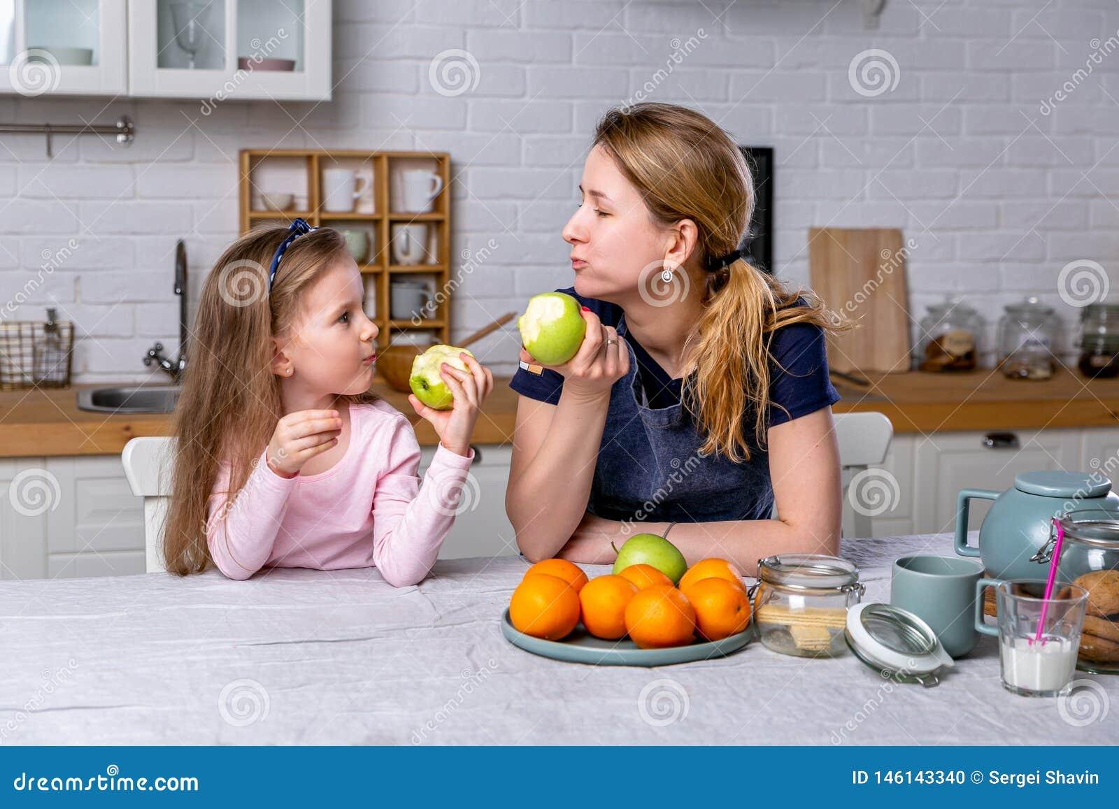 愉快的女孩和她美丽的年轻母亲一起食用早餐在一个白色厨房 他们获得乐趣并且吃着苹果