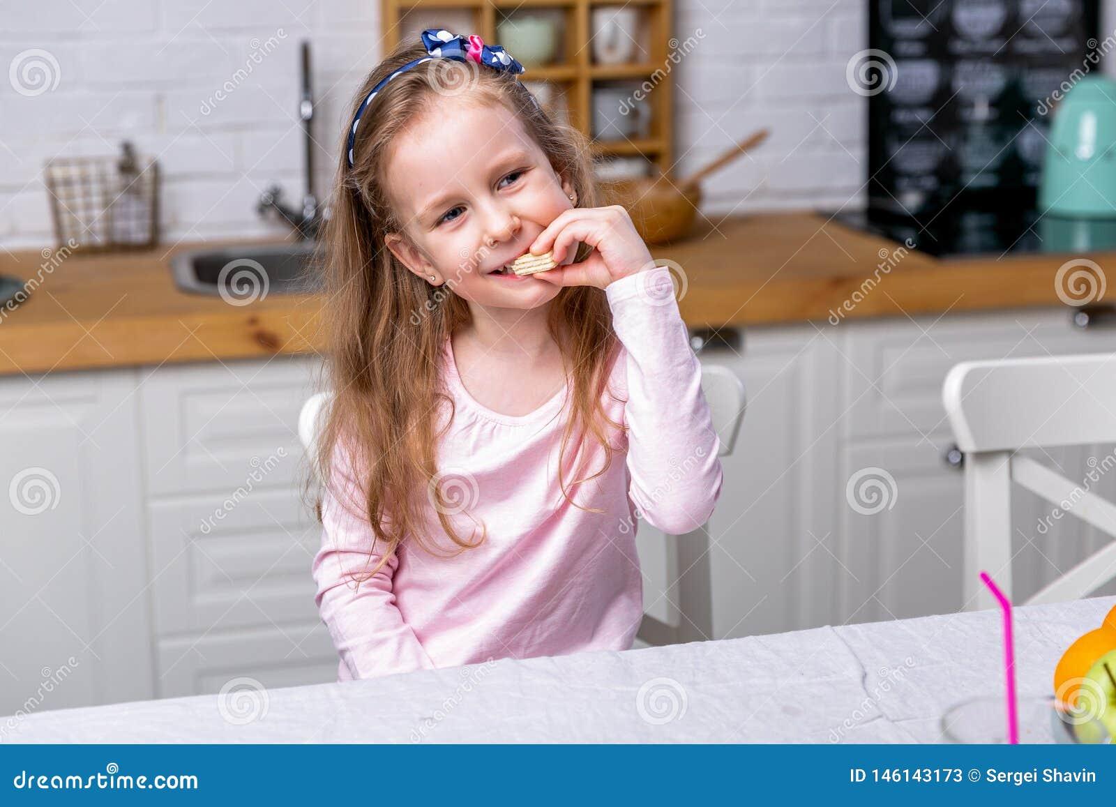 愉快的女孩食用早餐在一个白色厨房 她吃奶蛋烘饼和微笑 E