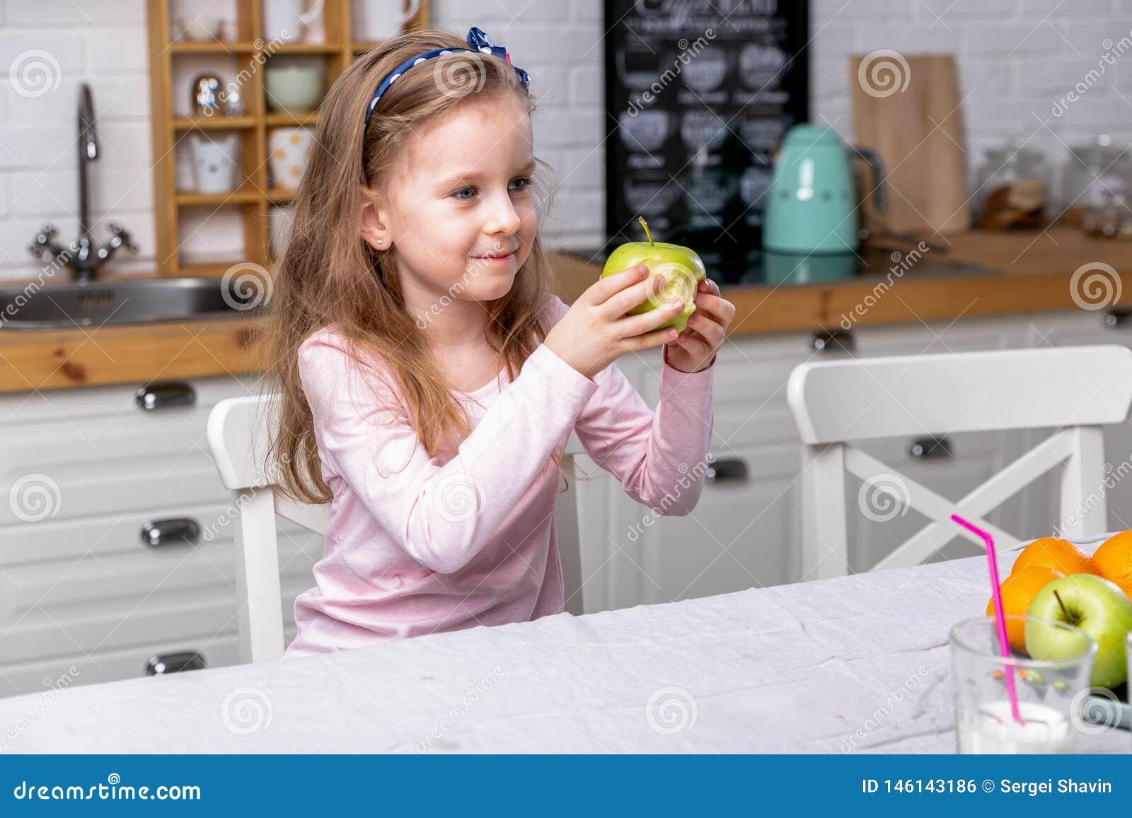 愉快的女孩食用早餐在一个白色厨房 她吃苹果和微笑 E