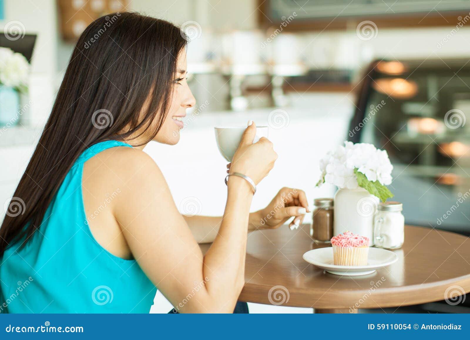 愉快的女孩饮用的咖啡