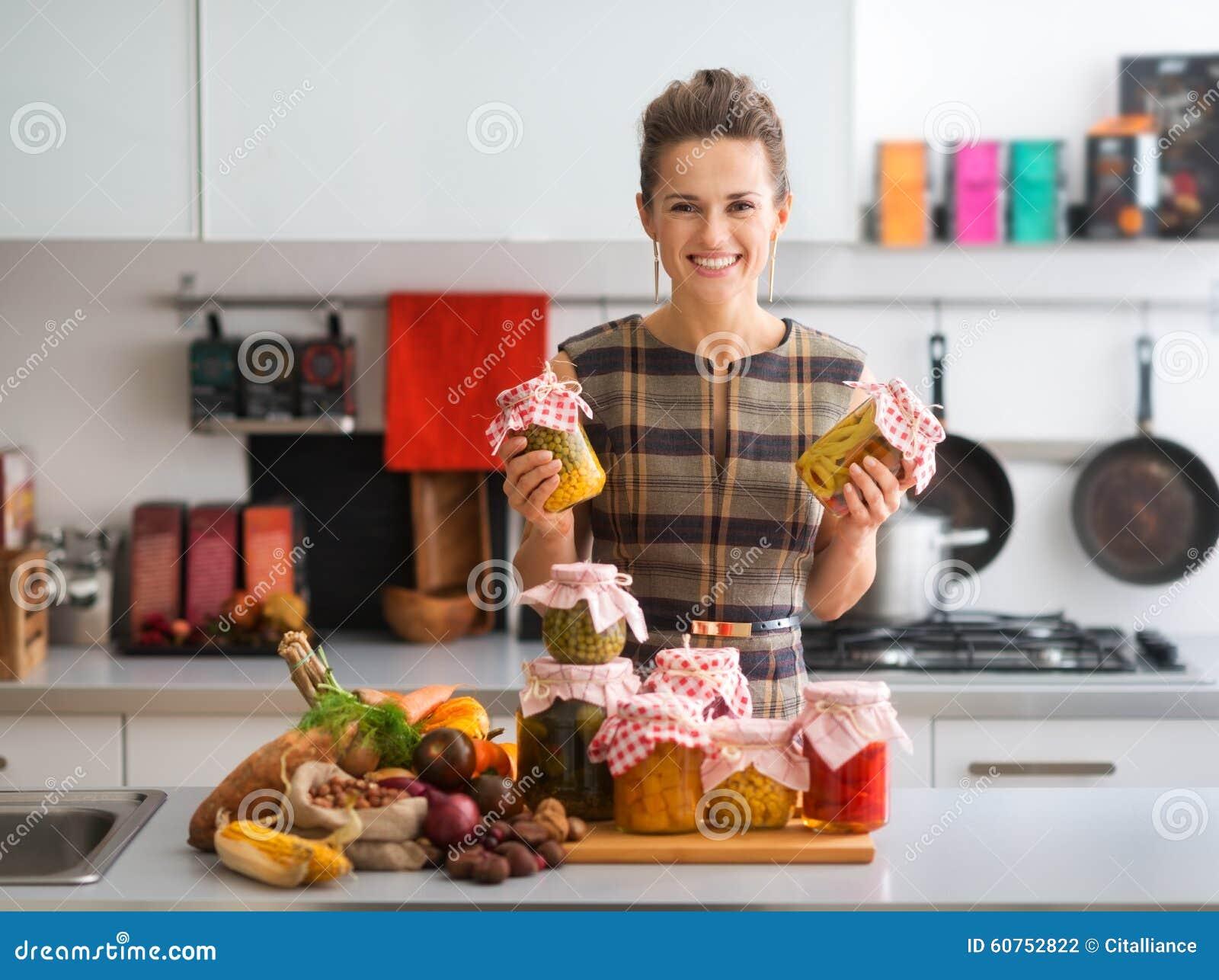 愉快的妇女在拿着瓶子被保存的菜的厨房里
