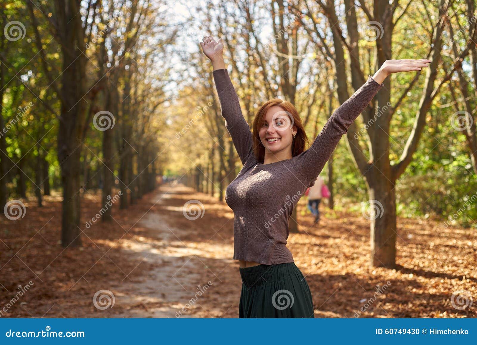 愉快的妇女在秋天公园