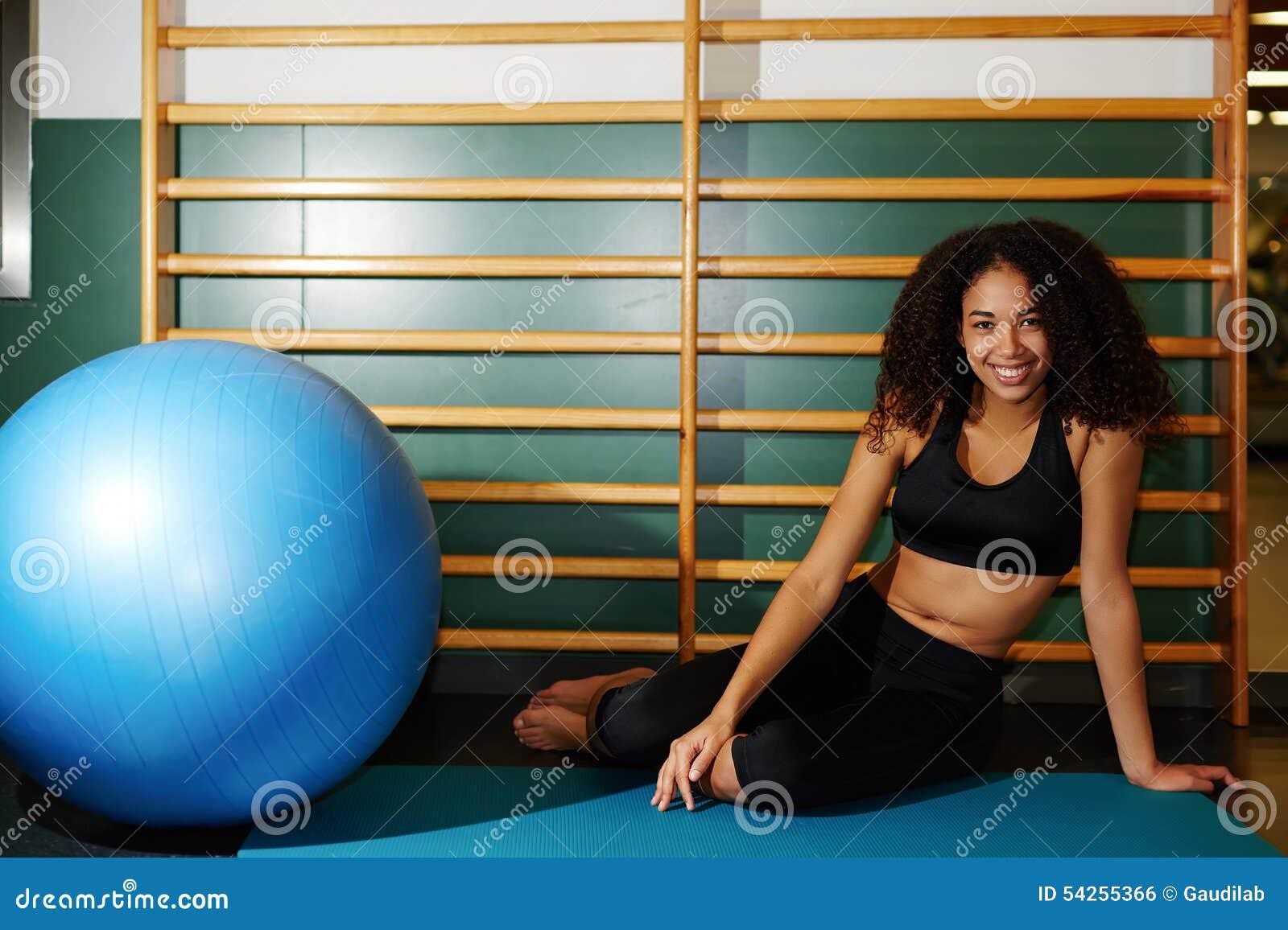 愉快的妇女坐席子有休息在健身训练以后在健身房