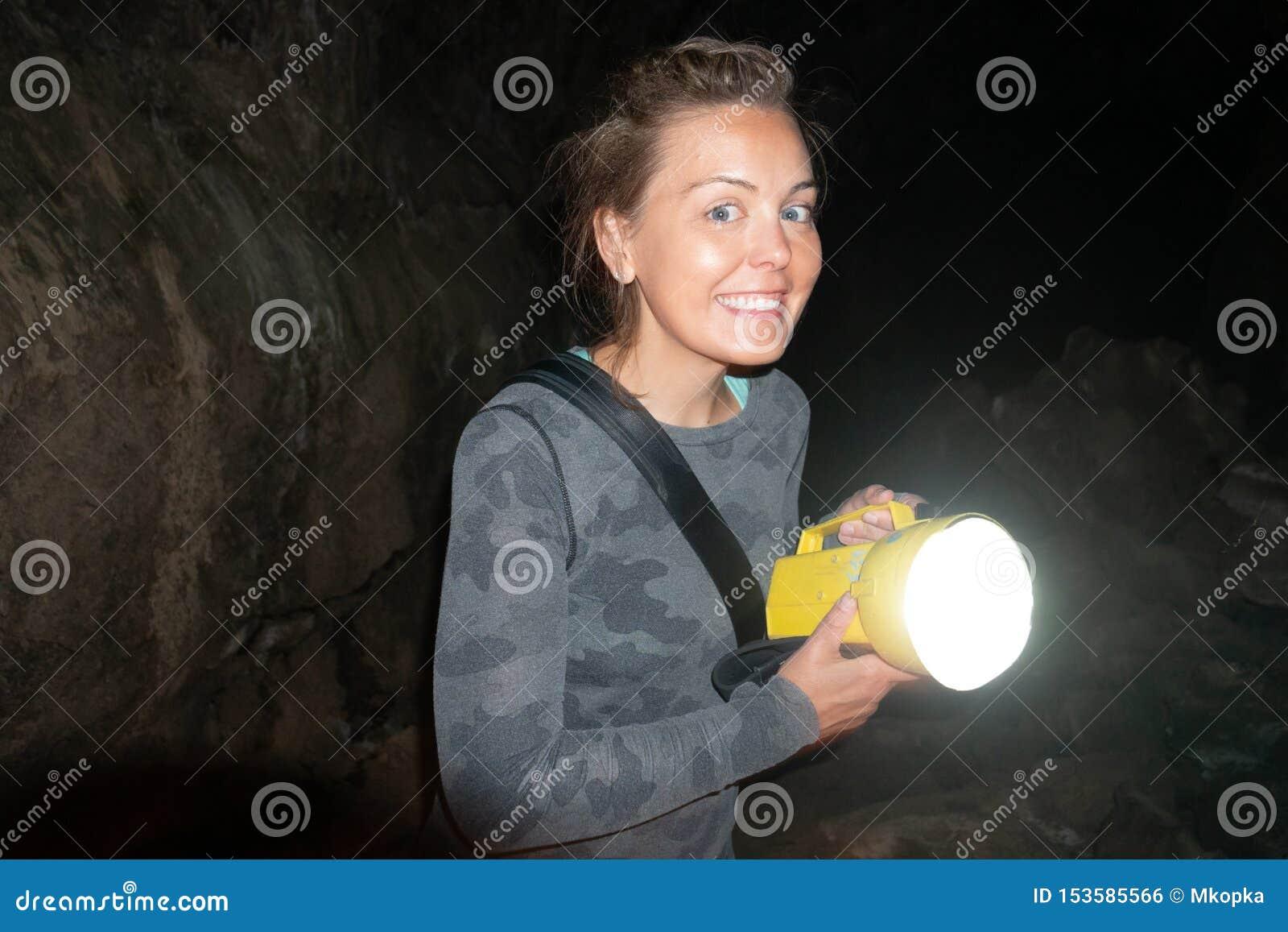 愉快的妇女探险家在加利福尼亚时拿着一个手电,当陷下和spelunking地下在火山岩床国家历史文物
