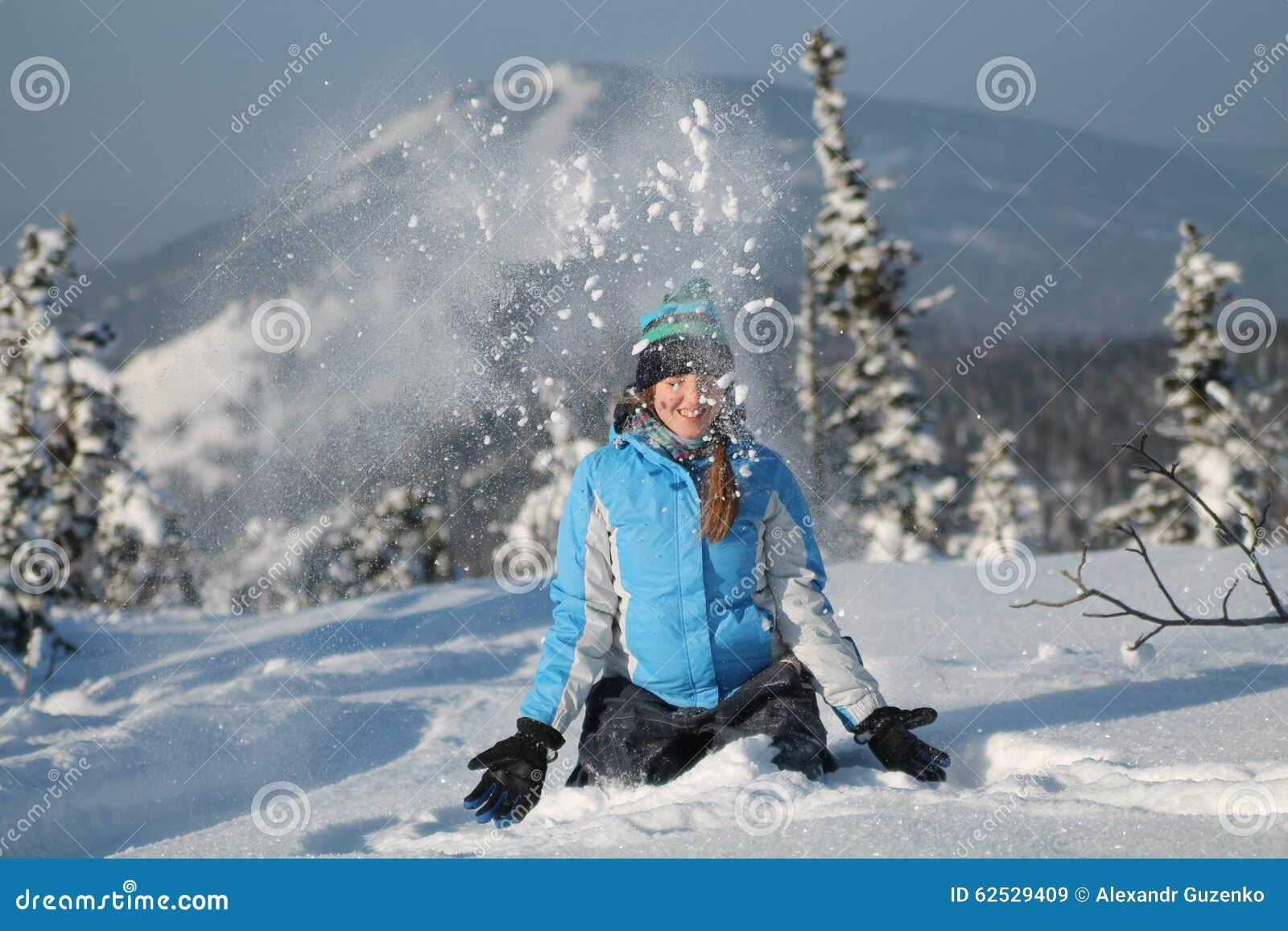 愉快的妇女跳跃在冬天山的,活跃女性享用的自然,