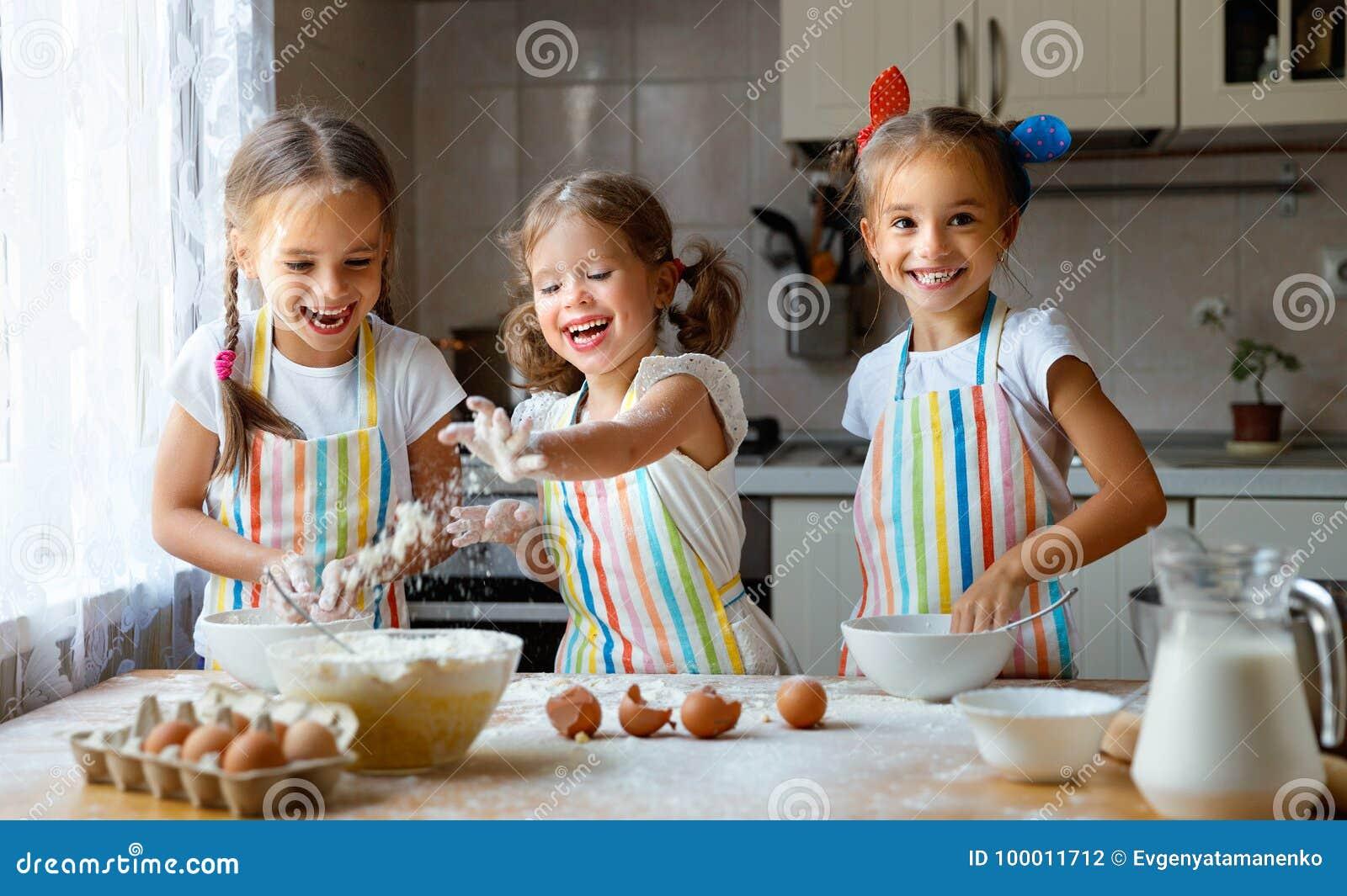 愉快的姐妹儿童女孩烘烤曲奇饼,揉面团,戏剧机智