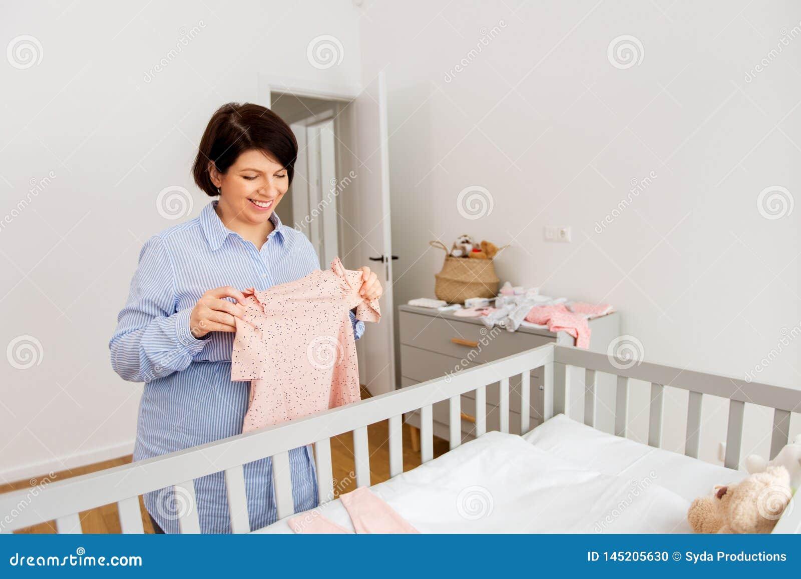 愉快的孕妇设置婴孩衣裳在家