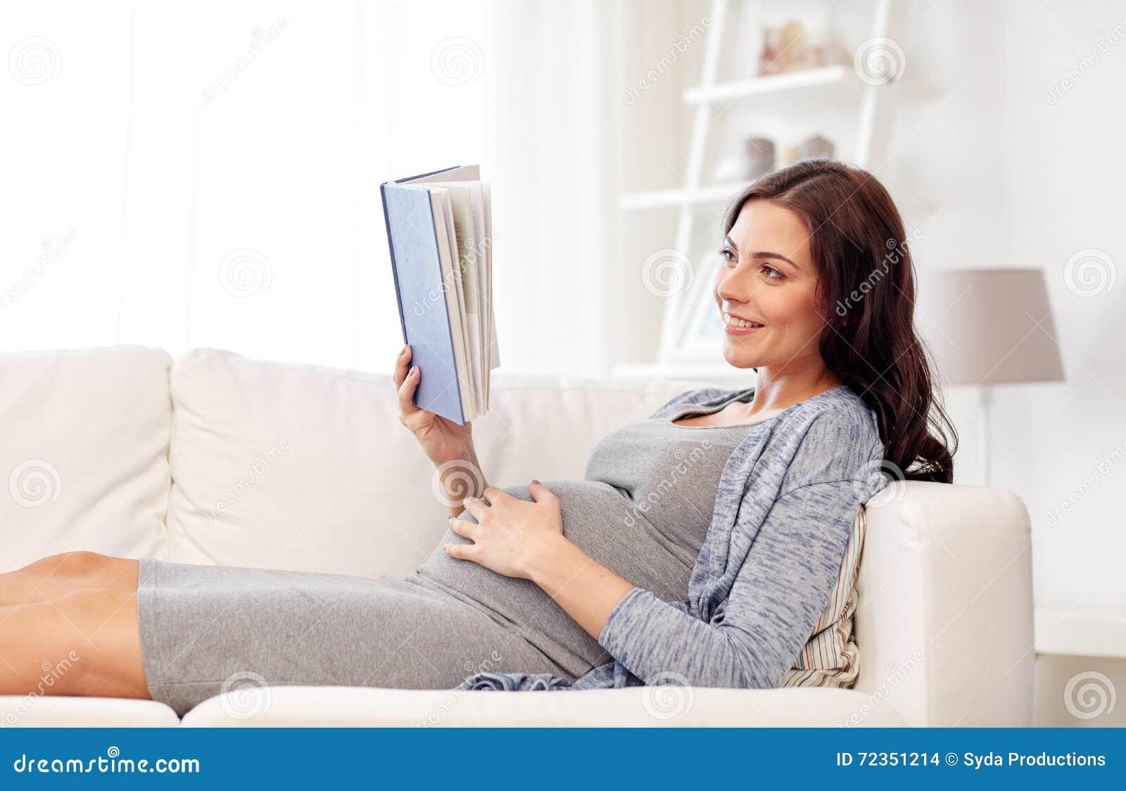 愉快的孕妇阅读书在家
