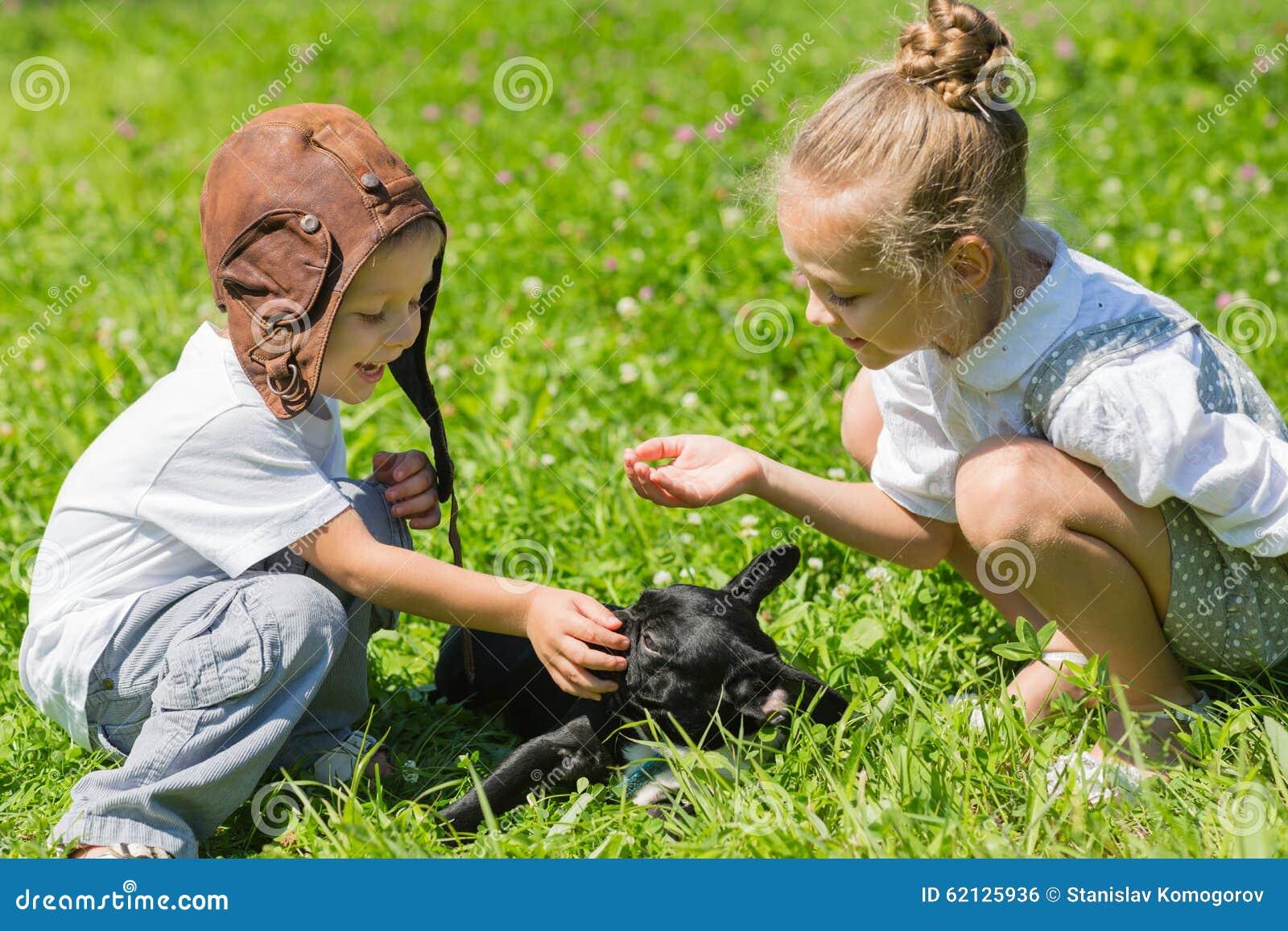 使用与狗(法国牛头犬)的愉快的孩子在草 背景兄弟查出的姐妹白色.图片