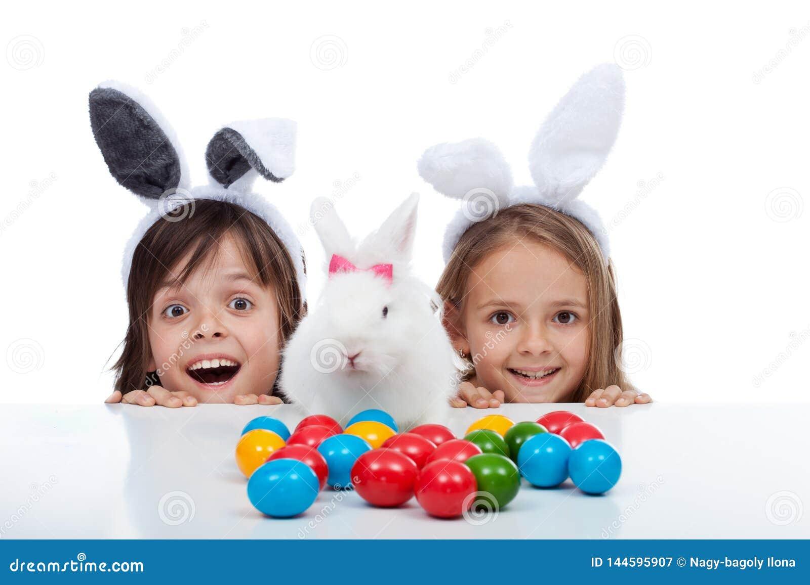 愉快的孩子发现了在白色和蛋死的站点-隔绝的复活节兔子