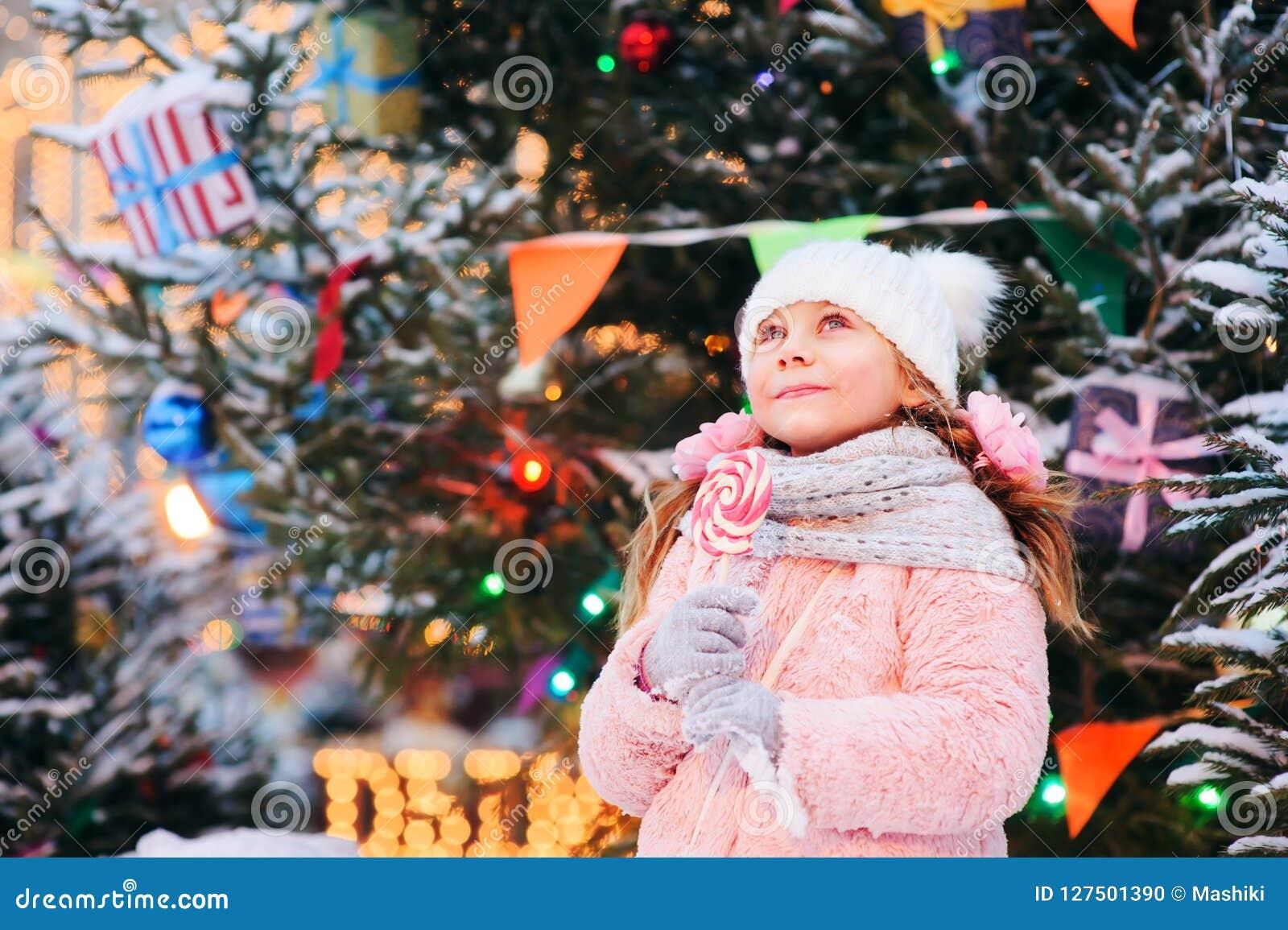 愉快的孩子女孩用圣诞节糖果 在圣诞树的寒假画象