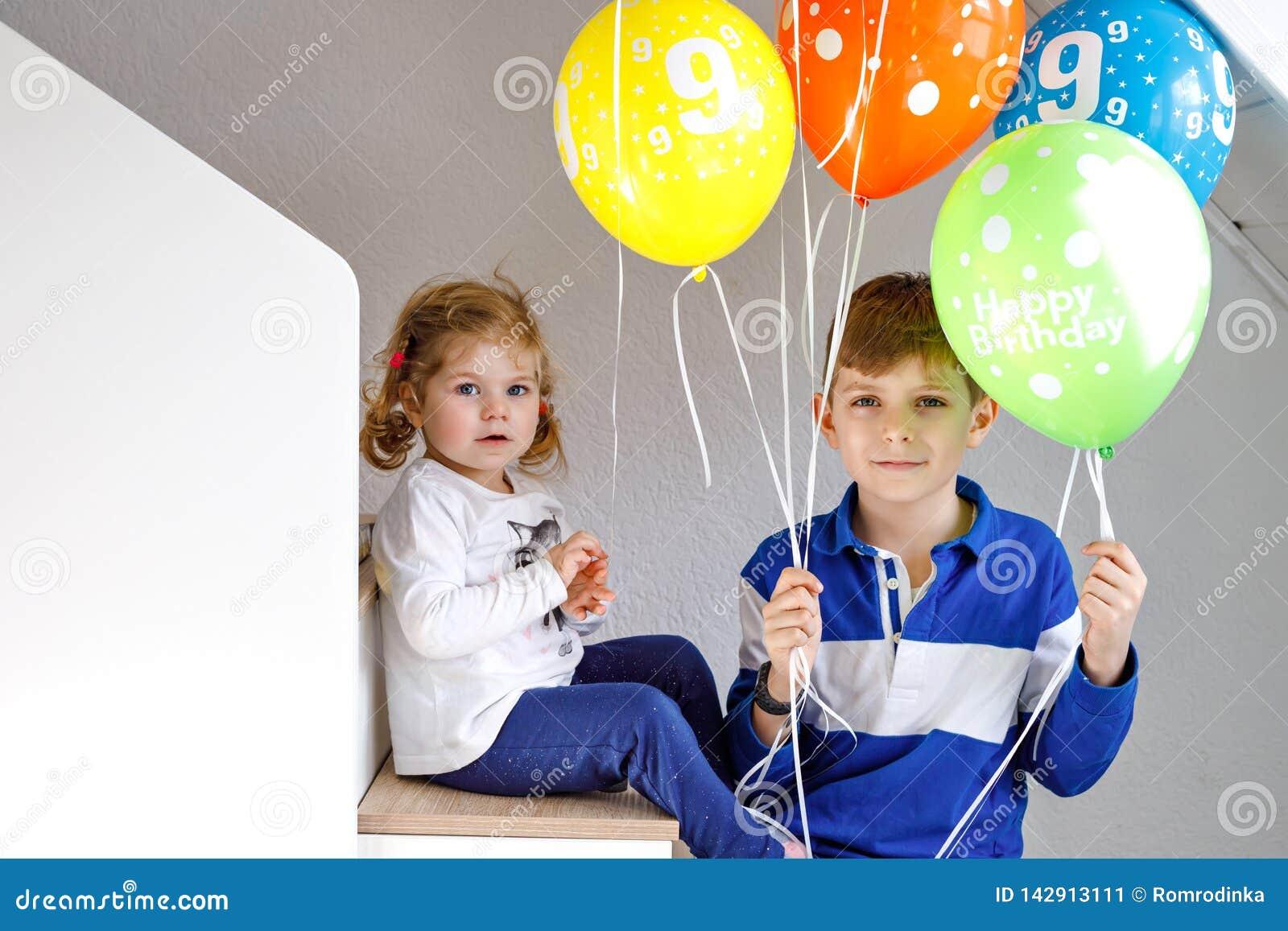 愉快的孩子男孩和逗人喜爱的矮小的小孩女孩画象有束的在五颜六色的气球在生日 愉快微笑