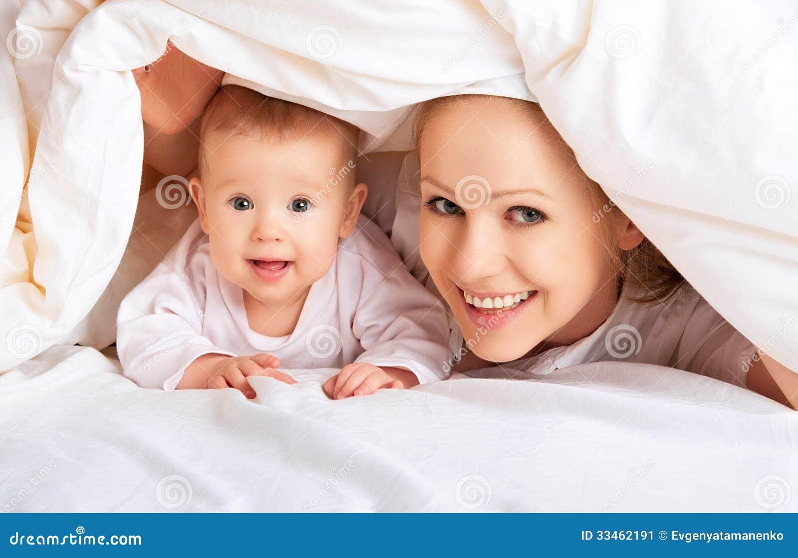 愉快的家庭。使用在毯子下的母亲和婴孩