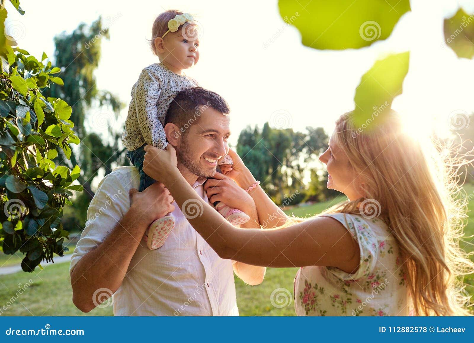 愉快的家庭在一个公园在夏天秋天