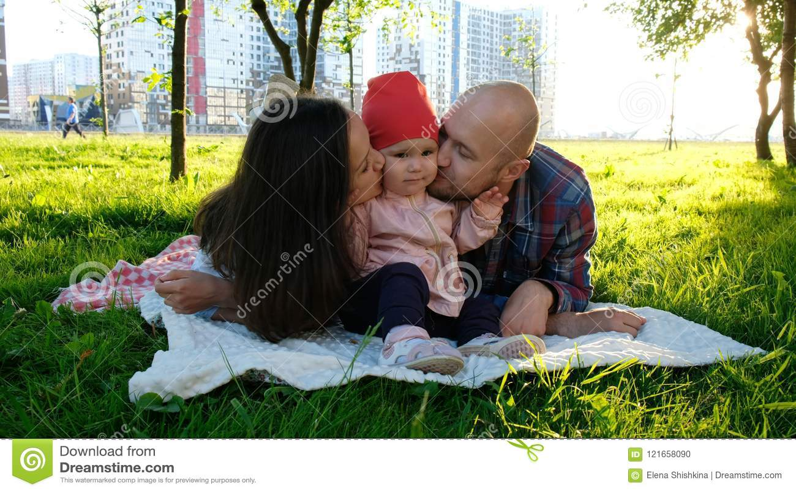 愉快的家庭在草说谎在夏天公园 父母亲吻面颊的一个小女婴在双方