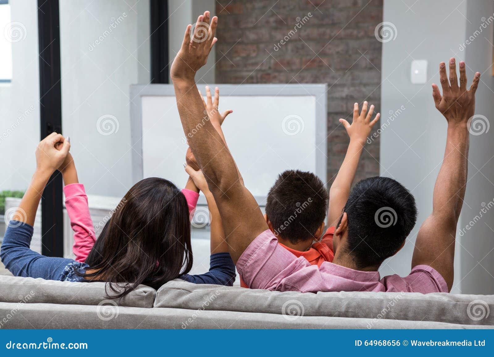 愉快的家庭欣喜,当看在沙发时的电视