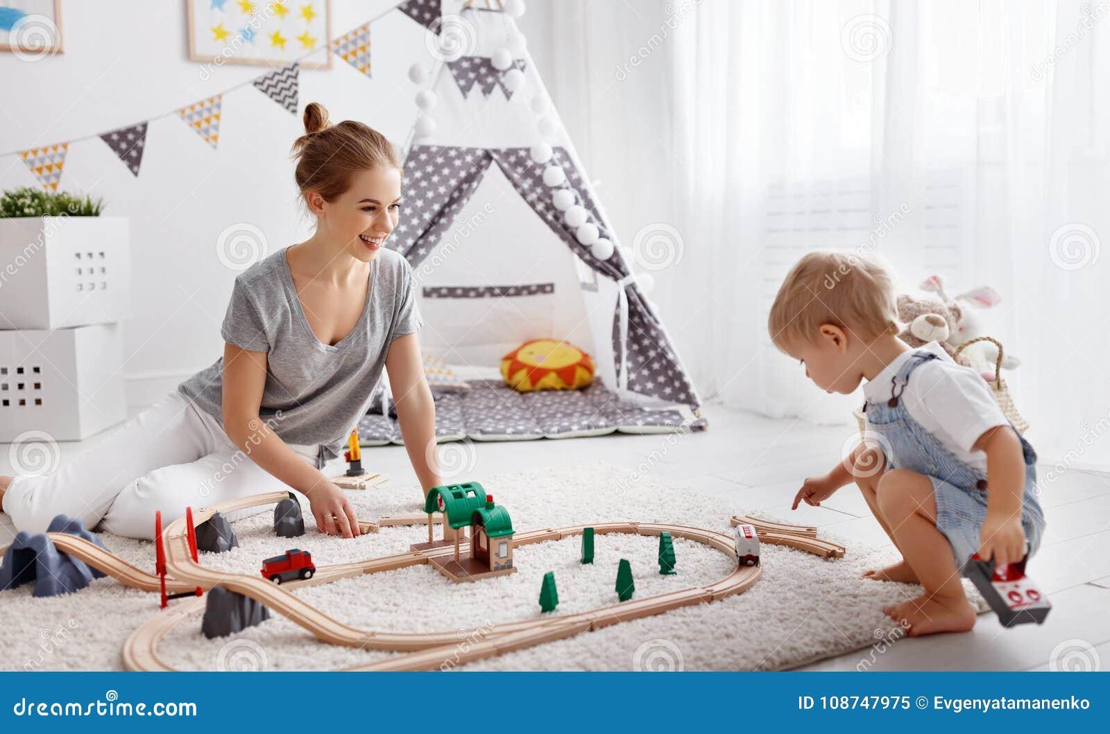 愉快的家庭母亲和使用在pl的玩具铁路的儿童儿子
