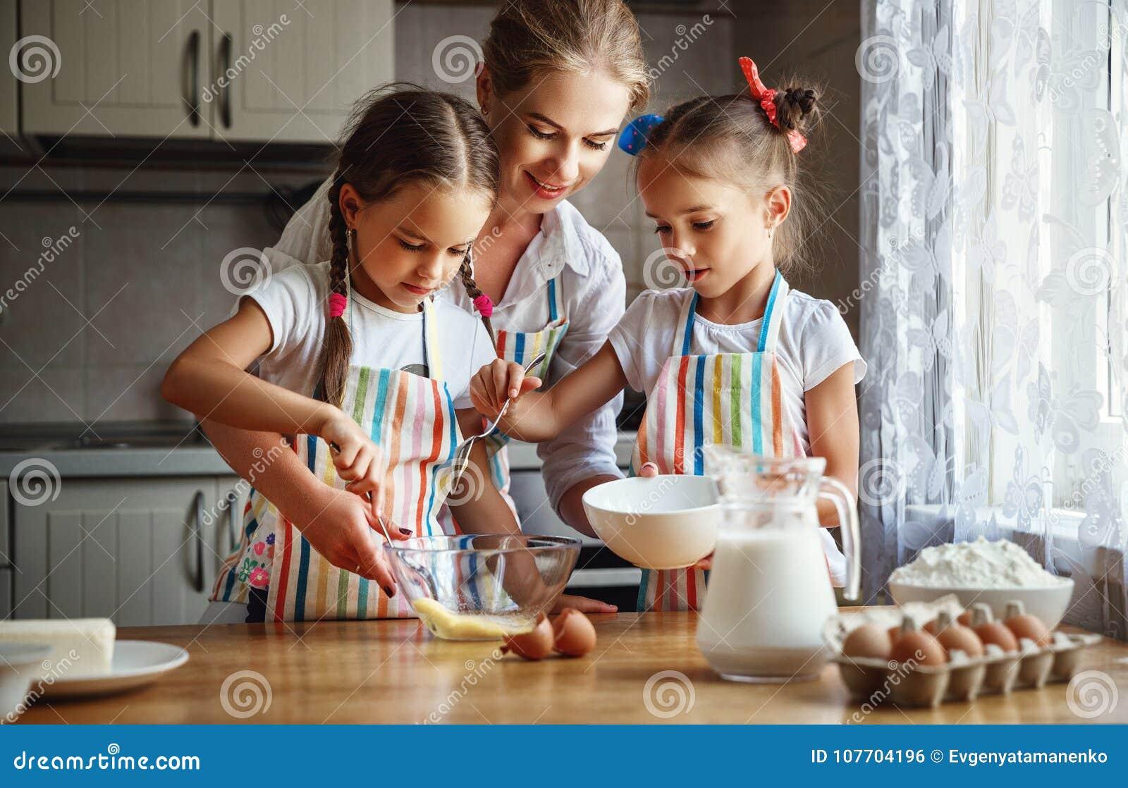 愉快的家庭母亲和儿童孪生烘烤揉的面团