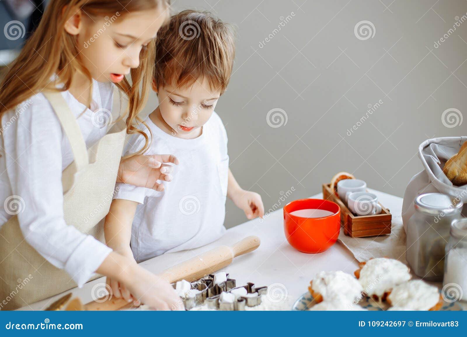 愉快的家庭滑稽的孩子在厨房里准备面团,烘烤曲奇饼