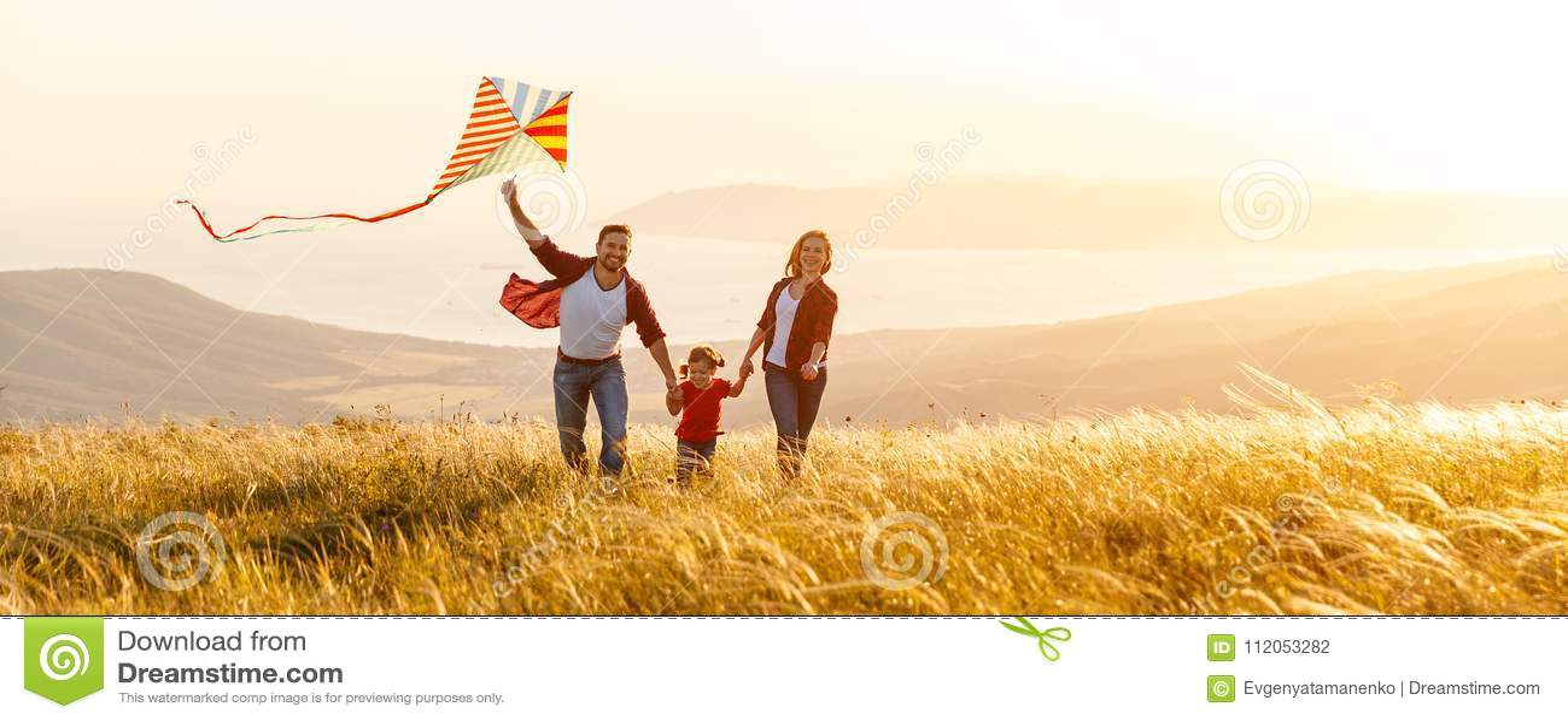 愉快的家庭父亲、母亲和儿童女儿发射风筝