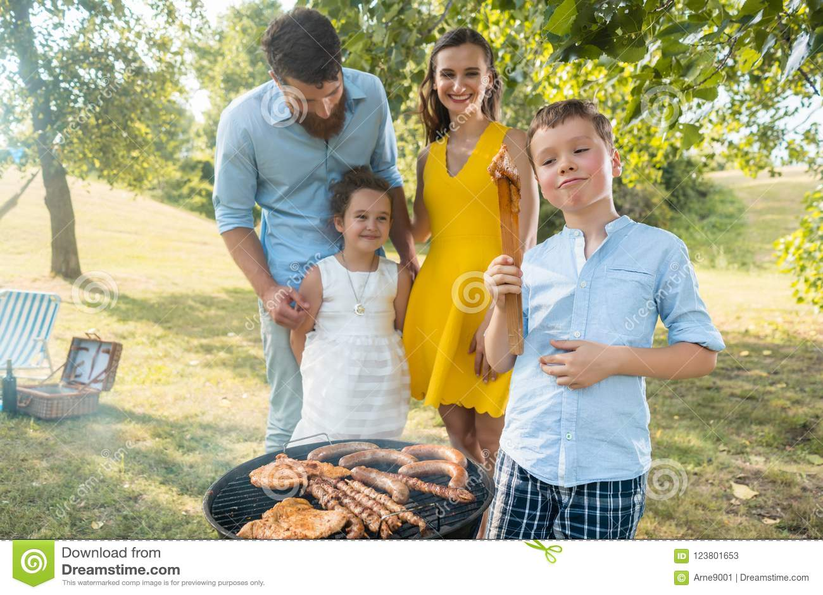 愉快的家庭画象有站立户外在烤肉附近的两个孩子的