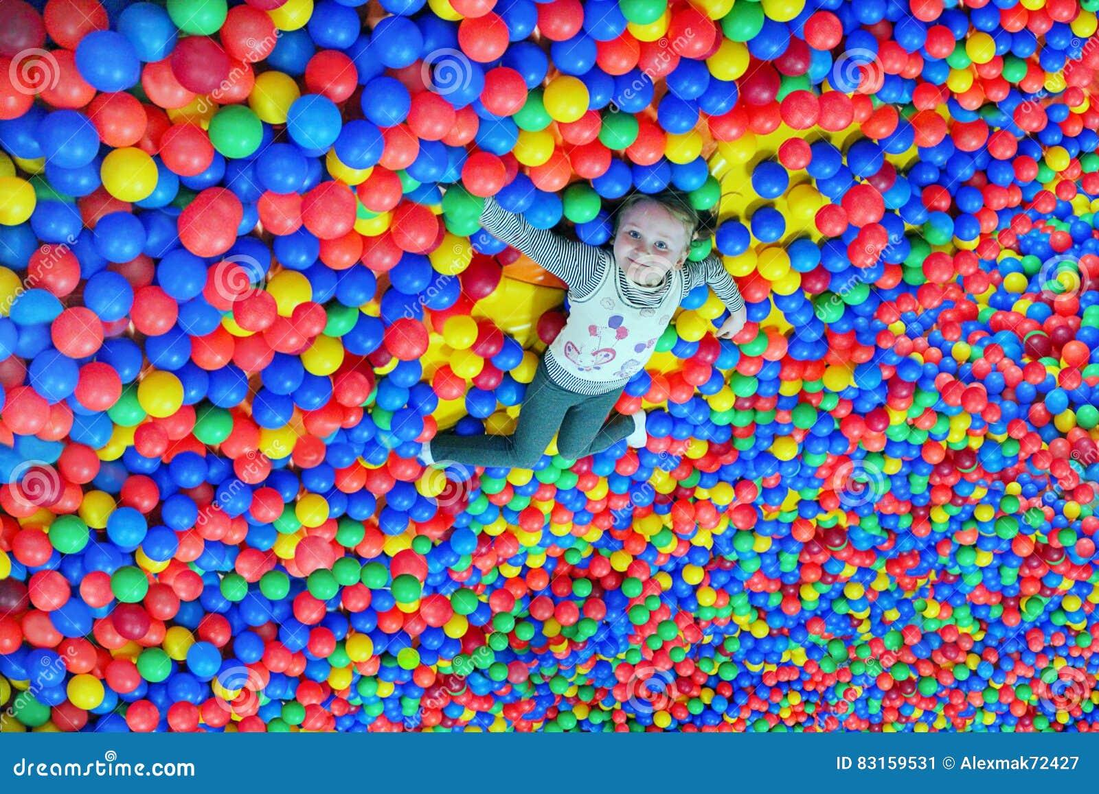 愉快的小女孩在多彩多姿的小球大堆放置