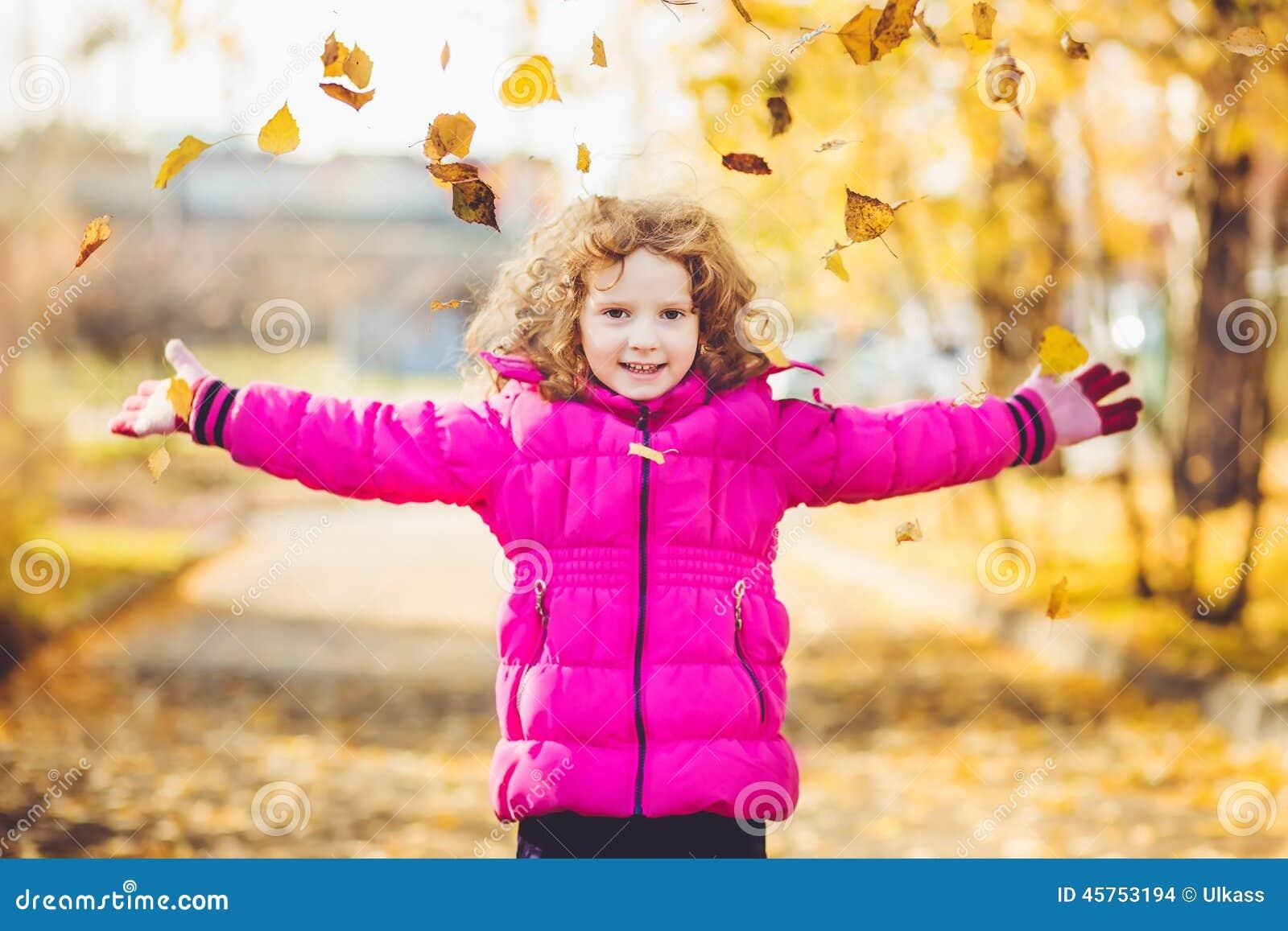 愉快的小女孩在天空中投掷秋叶