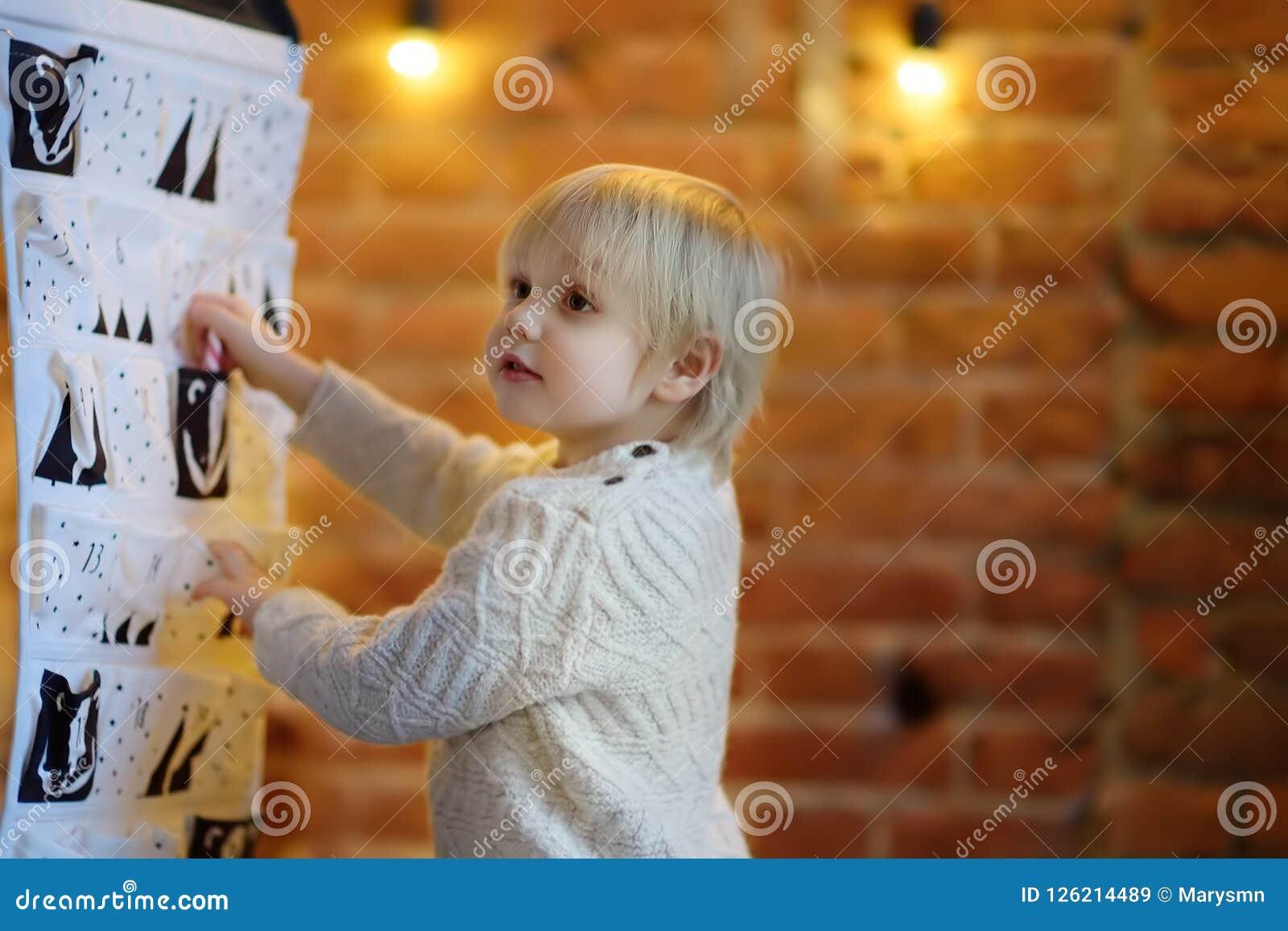 愉快的小男孩采取从出现日历的甜点自圣诞前夕